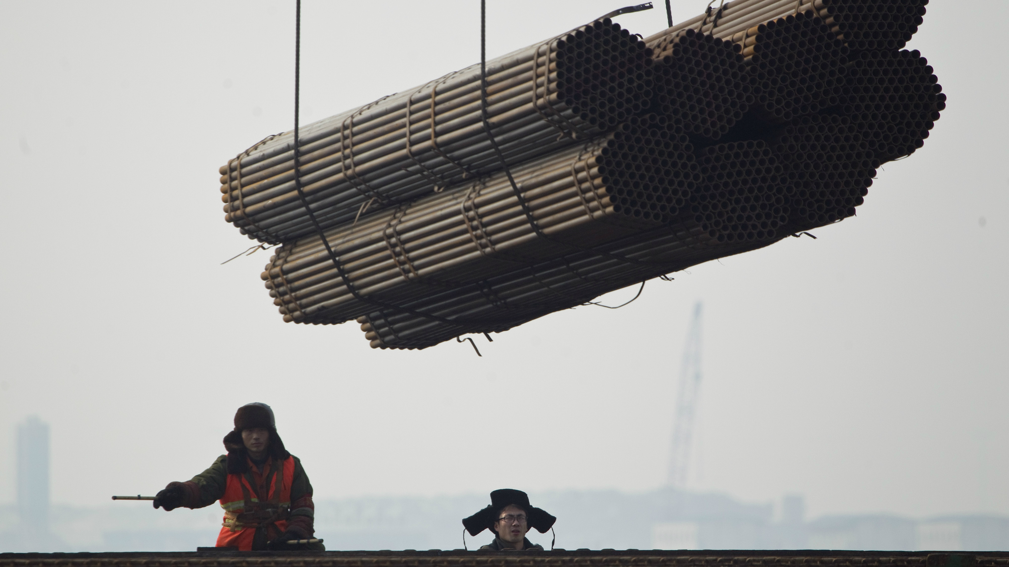 Port workers watch as steel pipes are loaded onto a freighter ship at Cao Feidian Port in Tangshan, in northern China's Hebei province, Monday, Feb. 20, 2012. (AP Photo/Alexander F. Yuan