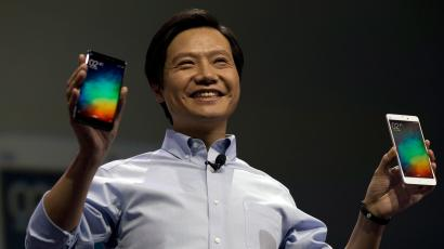 Lei Jun, chairman of Chinese smartphone maker Xiaomi, holds up the latest models of the Xiaomi Note at a press event in Beijing, Thursday, Jan. 15, 2015. The Chinese manufacturer on Thursday unveiled a new model that Lei said has processor size and performance comparable to Apple's iPhone 6 but is thinner and lighter. (AP Photo/Ng Han Guan)