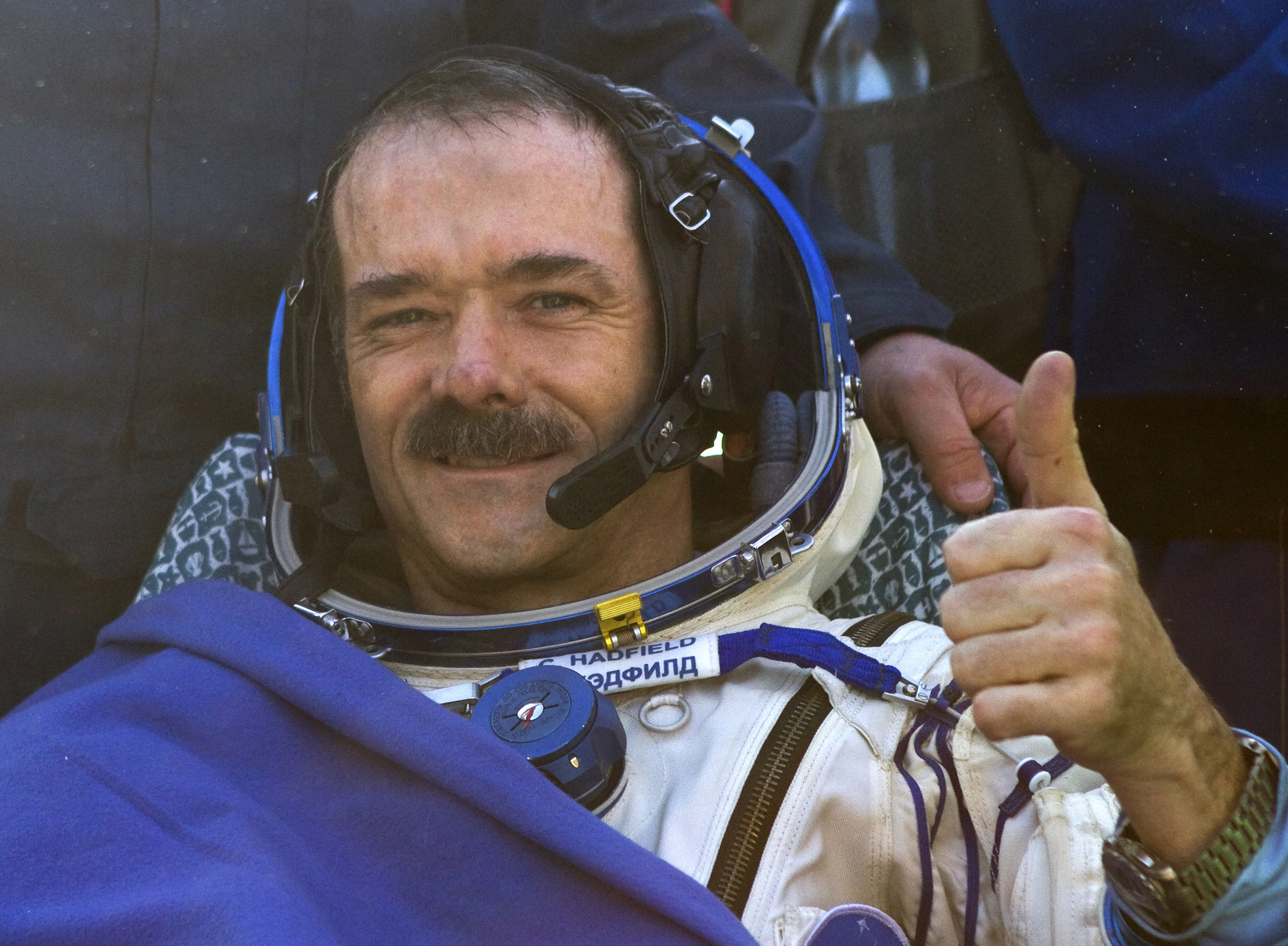 Canadian astronaut Chris Hadfield gestures after the Russian Soyuz space capsule landed some 150 kilometers (94 miles) southeast of the town of Dzhezkazgan in central Kazakhstan, Tuesday, May 14, 2013. The Soyuz space capsule carrying a three-man crew returning from a five-month mission to the International Space Station landed safely Tuesday on the steppes of kazakhstan. (AP Photo/ Sergei Remezov, Pool)