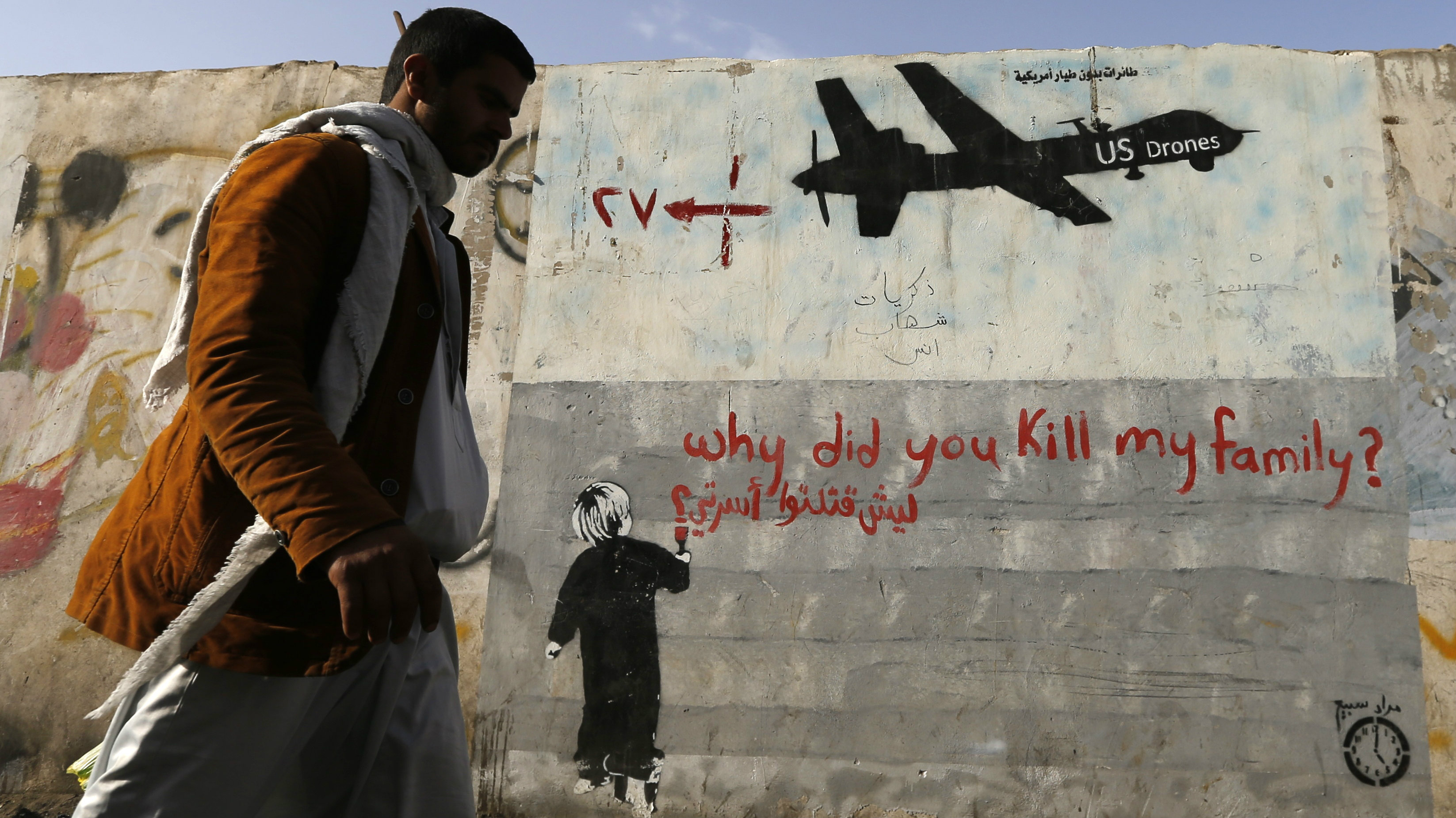 A man walks past a graffiti, denouncing strikes by U.S. drones in Yemen, painted on a wall in Sanaa November 13, 2014. Yemeni authorities have paid out tens of thousands of dollars to victims of drone strikes using U.S.-supplied funds, a source close to Yemen's presidency said, echoing accounts by legal sources and a family that lost two members in a 2012 raid.