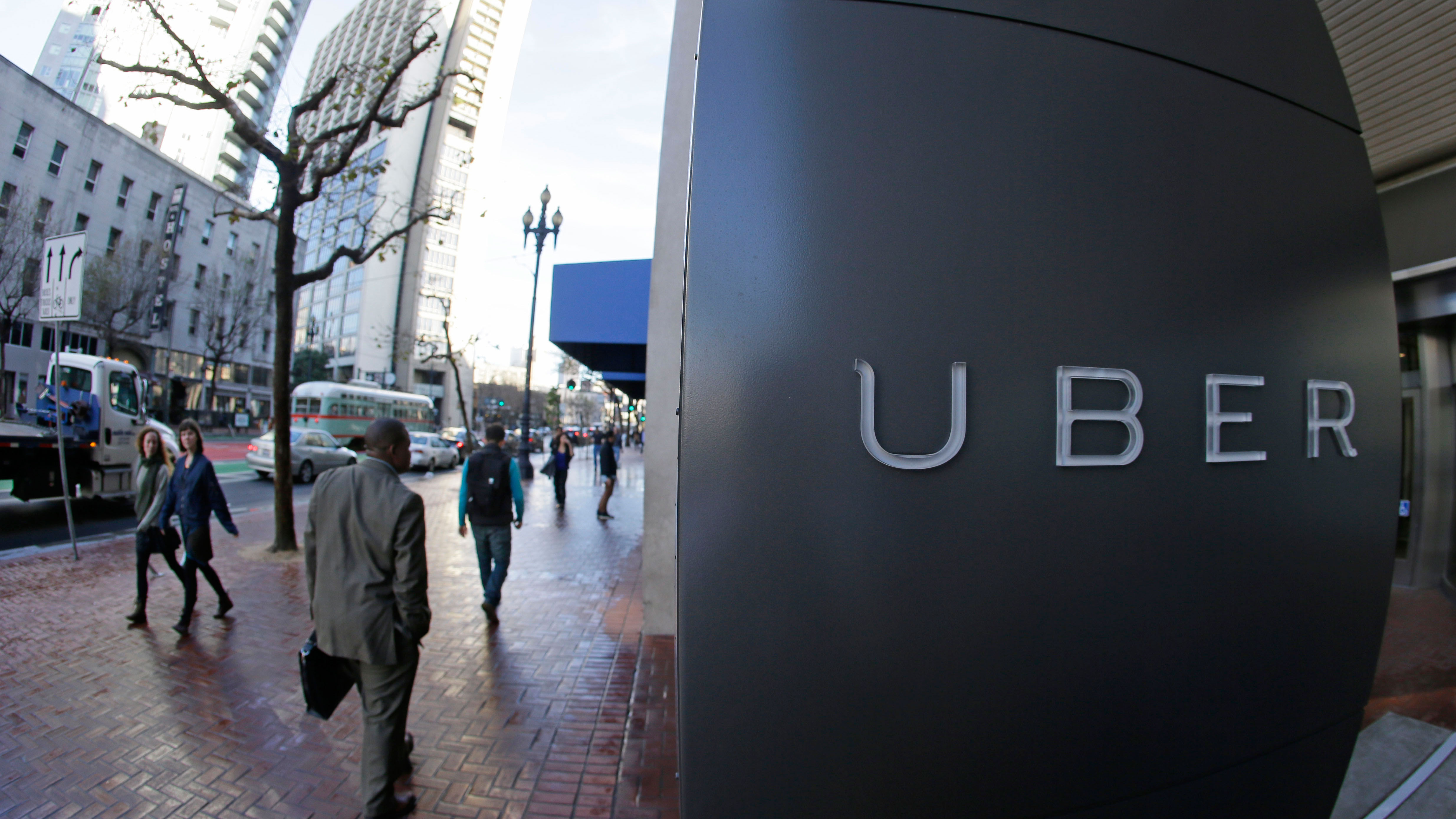 In this photo taken Tuesday, Dec. 16, 2014, people go past the headquarters of Uber in San Francisco. (AP Photo/Eric Risberg)