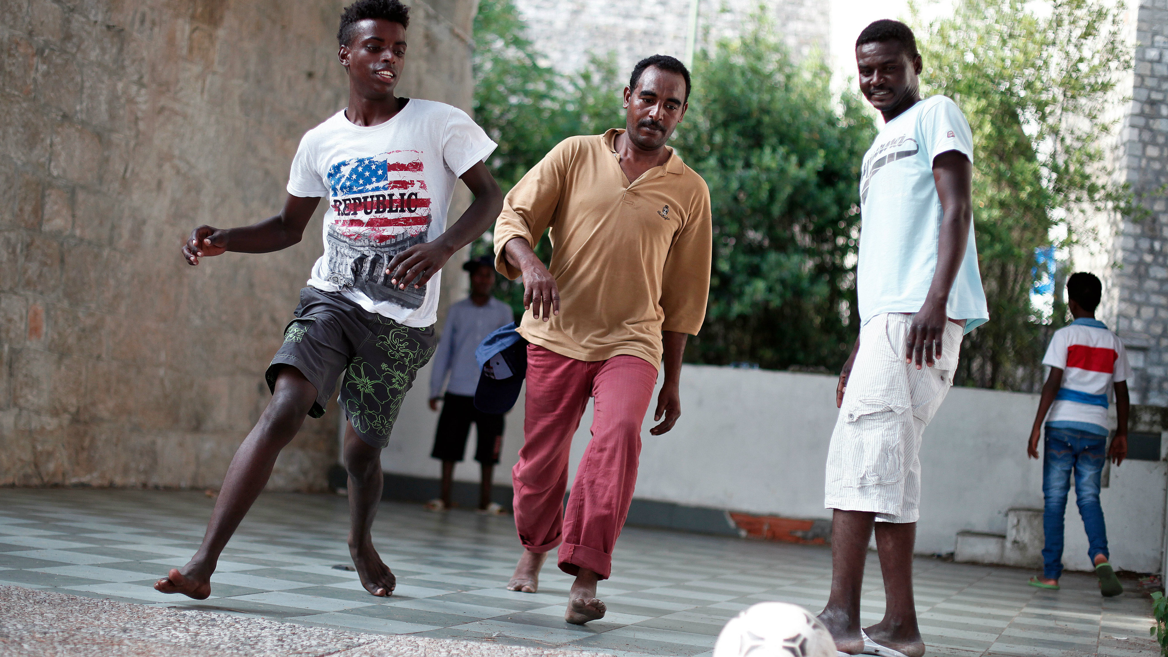 Hassen Hamza, 32, from Sudan, center, and Abraham Hilan 17, from Eritrea, left, play soccer at the Franco-Italian border in Ventimiglia, Italy, Sunday, June 21, 2015. European Union nations failed to bridge differences Tuesday, June 16 over an emergency plan to share the burden of the thousands of refugees crossing the Mediterranean Sea, while on the French-Italian border, police in riot gear forcibly removed dozens of migrants. (AP Photo/Thibault Camus)