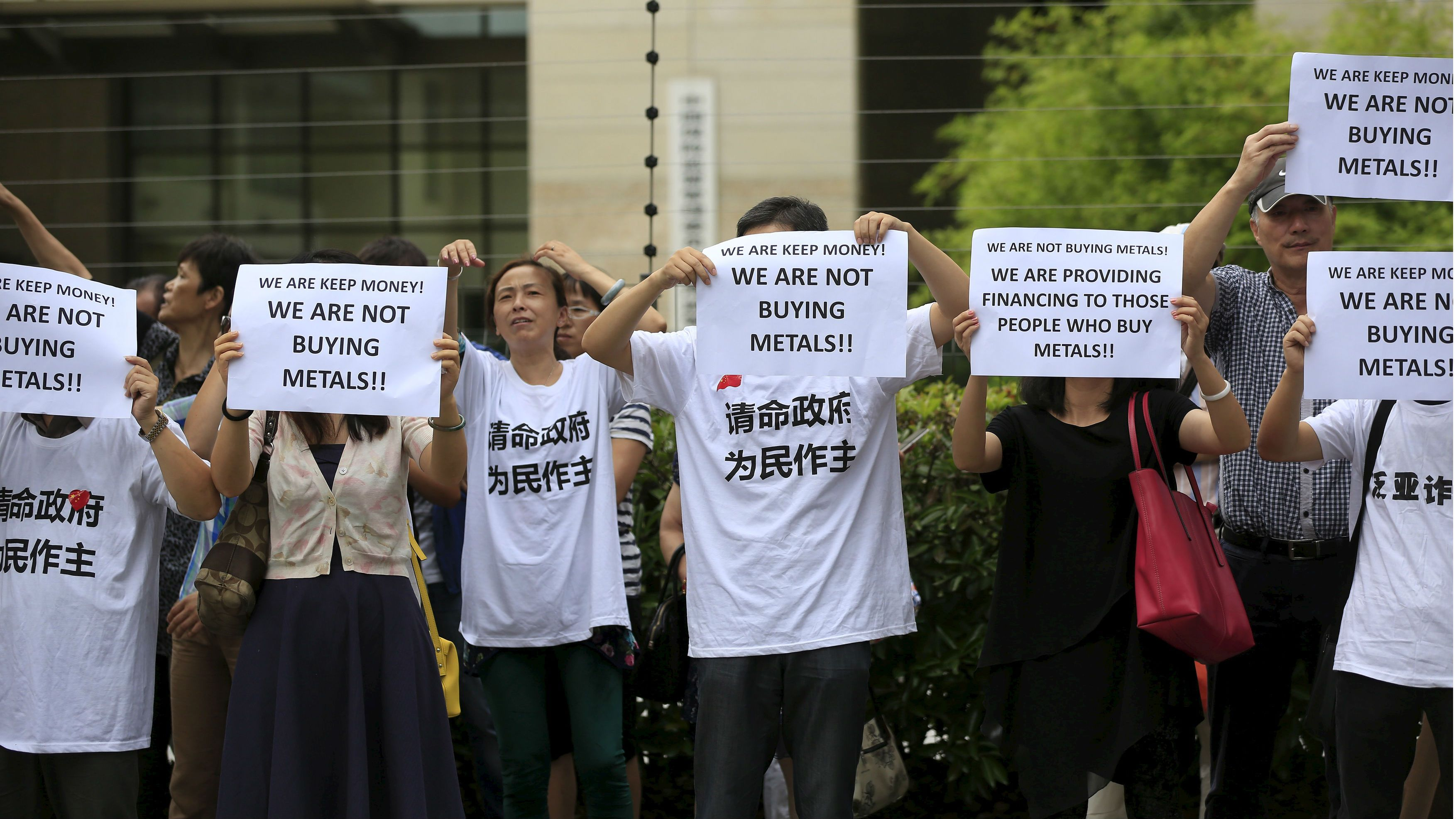 "Protesters holding papers gather outside the Shanghai Banking Regulatory Bureau to protest against the Fanya Metal Exchange, in Shanghai, China, September 25, 2015. Hundreds of investors gathered outside the headquarters of China's securities watchdog to protest against a metals exchange in a southwest province they accuse of defrauding them of billions of yuan. The Chinese characters on the shirts read, ""A plea to the government to stand judge for the people."" REUTERS/Aly Song"