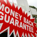 A sign offers a money back guarantee on the purchase of a home for sale in Moreland Hills, Ohio on Wednesday, July 30, 2008. Freddie Mac on Wednesday posted a second-quarter loss more than three-times larger than Wall Street expected as more homeowners fell behind on their mortgages. (AP Photo/Amy Sancetta)