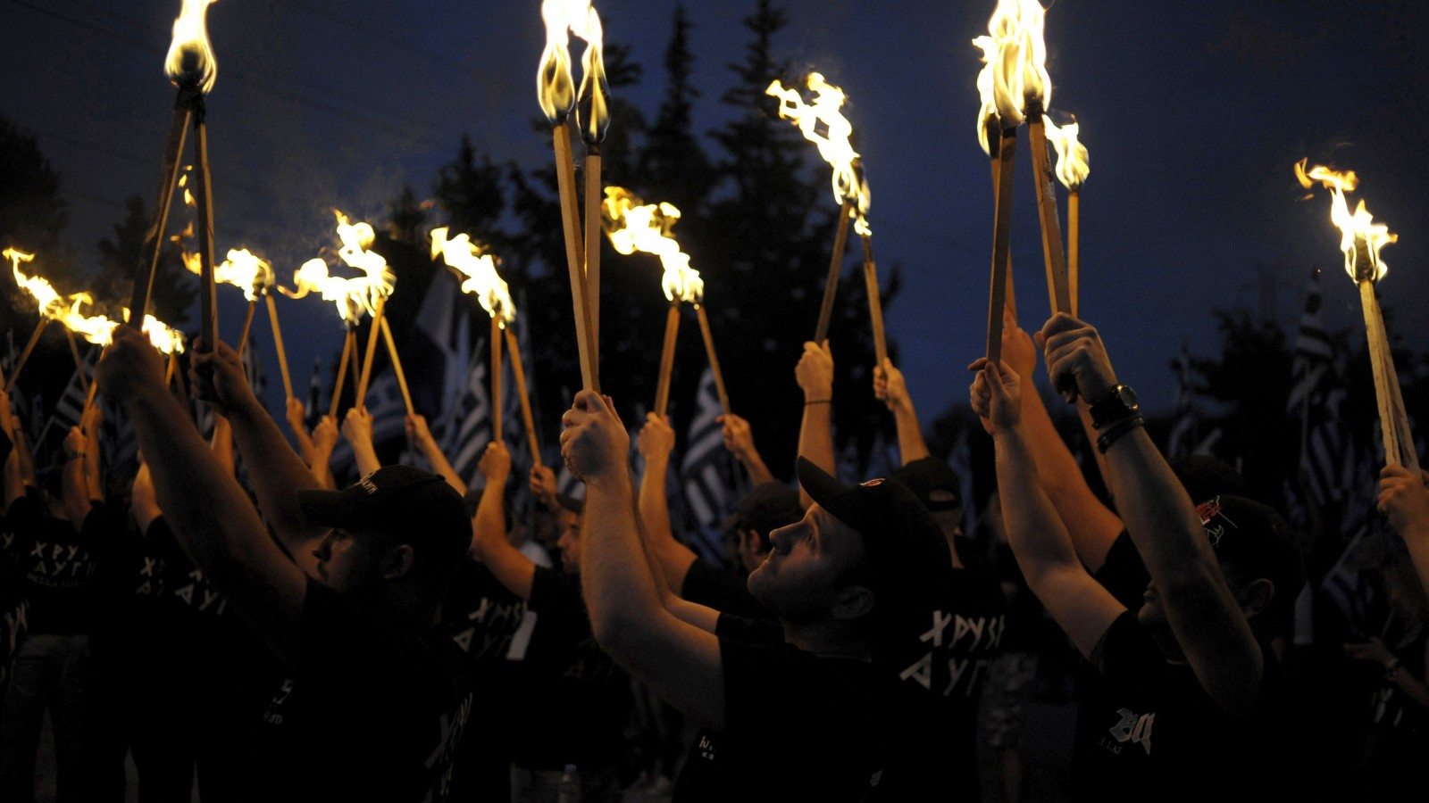 REFILE - CORRECTING BYLINEGolden Dawn supporters lift torches as they take part in a ceremony in Thermopylae, outside Athens, Greece, September 5, 2015.  Flaming torches raised, far-right Golden Dawn supporters dressed in black chanted the Greek national anthem as darkness fell on Thermopylae, where King Leonidas and 300 Spartans defied a vast Persian army in 480 BC. Standing before them, a member of the European Parliament from Golden Dawn, the euro zone's most extreme right-wing political party, roused the crowd with defiant denunciations of enemies at home and abroad ahead of a national election on September 20, 2015.  Picture taken September 5, 2015 REUTERS/Fotis Plegas G. - RTSMTB