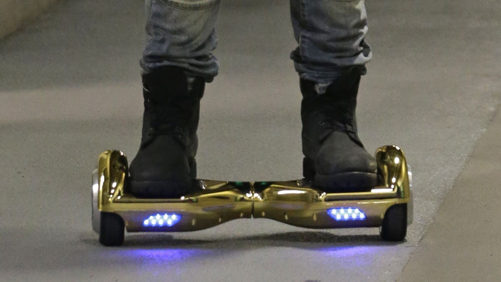 """Seattle Seahawks wide receiver B.J. Daniels rides through a hallway at CenturyLink Field on an electric self-balancing scooter commonly called a """"hoverboard,"""" as he arrives for an NFL football game against the Detroit Lions, Monday, Oct. 5, 2015, in Seattle. (AP Photo/Elaine Thompson)"""
