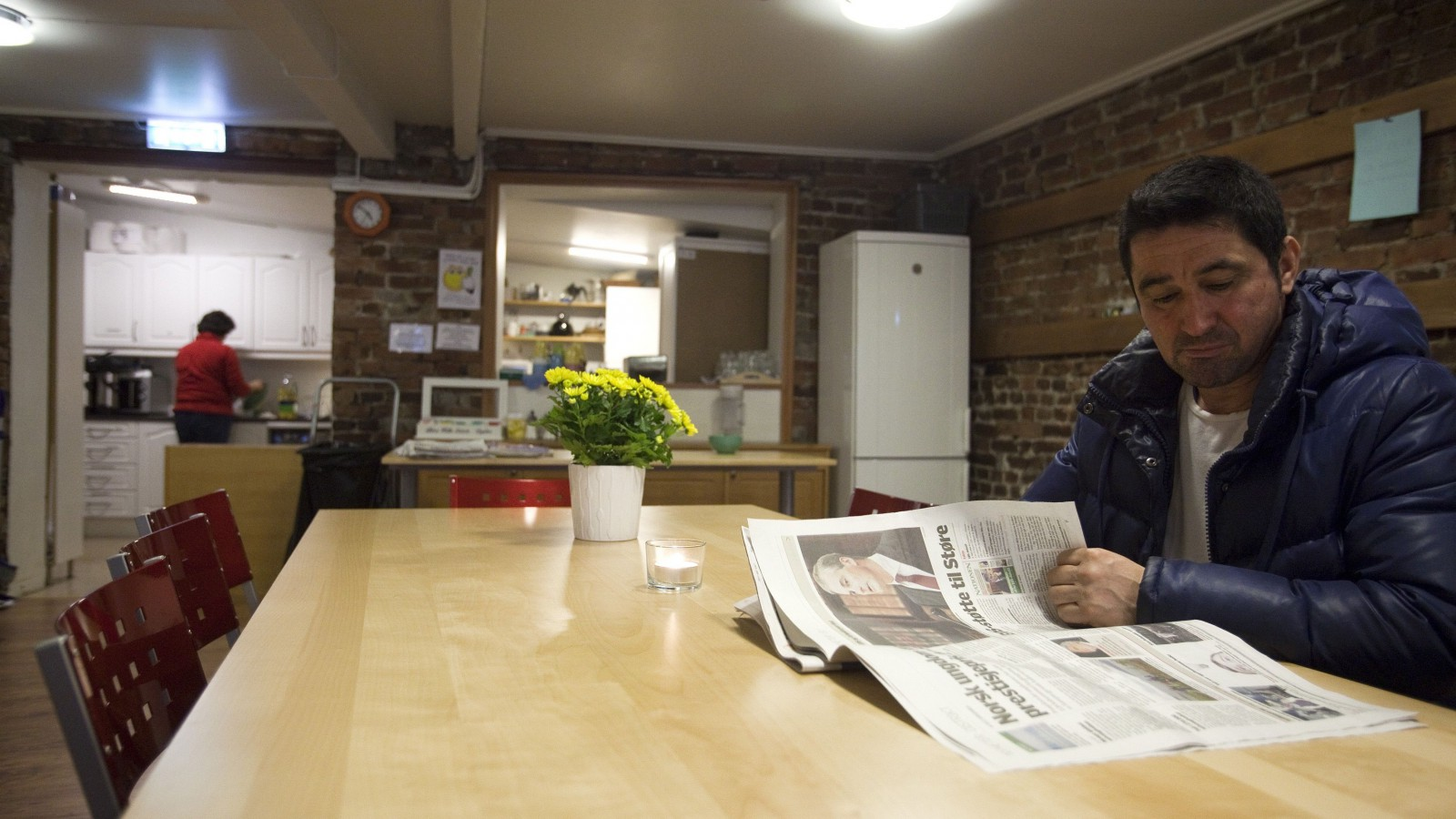 An immigrant from Spain, reads a newspaper at Robin Hood House, a centre that provides services to the economically disadvantaged