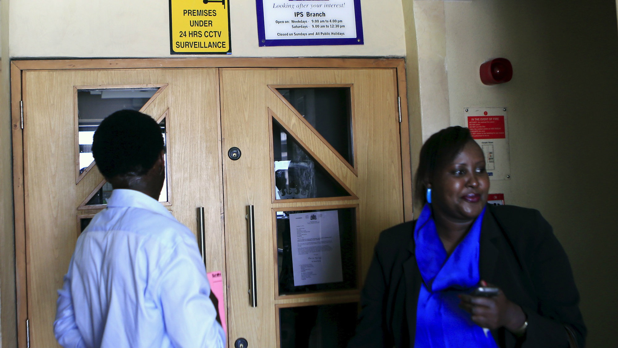 Customers of Imperial Bank wait outside a shuttered branch in Nairobi.