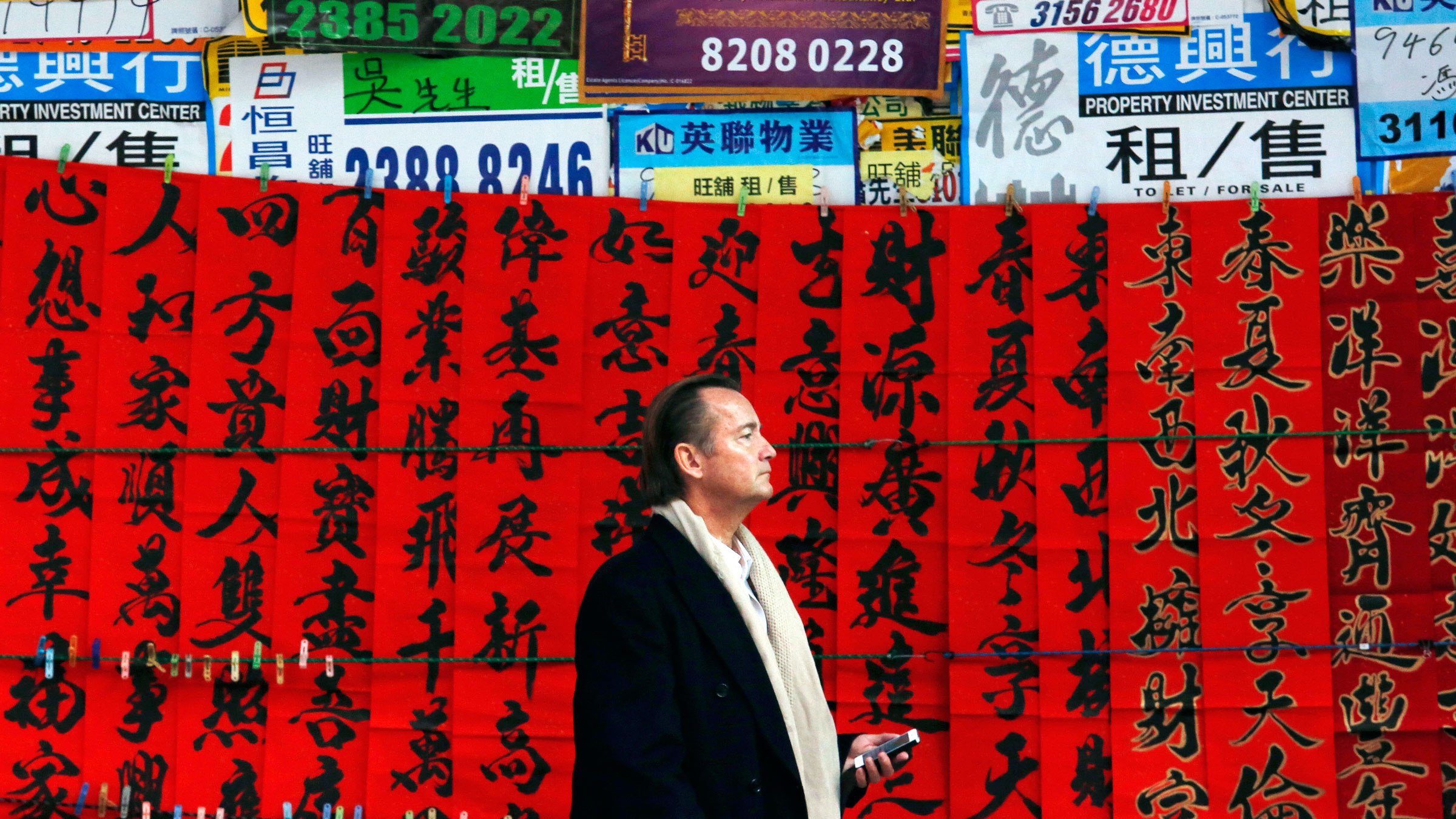 A man stands outside a closed shop covered with Chinese calligraphy on red papers to celebrate the upcoming Chinese New Year of the Goat in Hong Kong February 9, 2015.