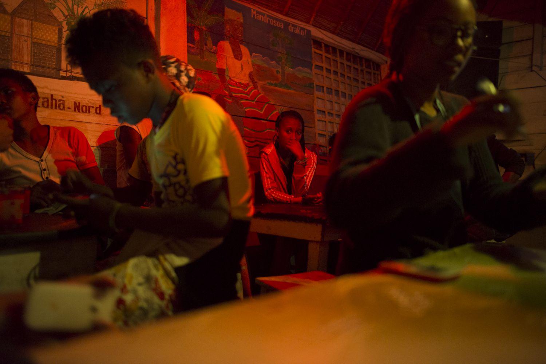 A woman sits alone in a karaoke bar in Manakara