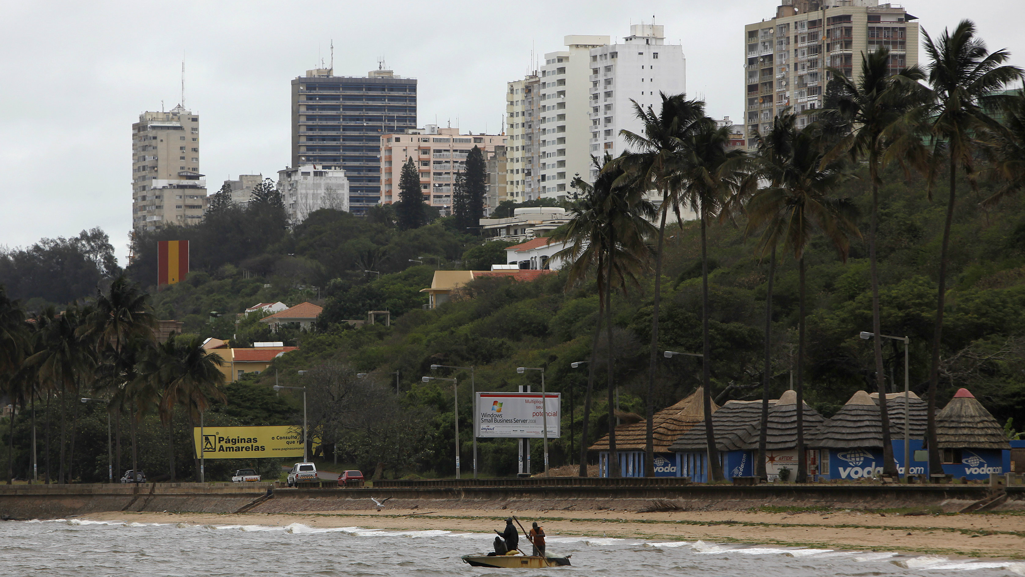 Fishermen cast their nets beneath the skyline of Mozambique's capital Maputo in this file picture taken November 2009