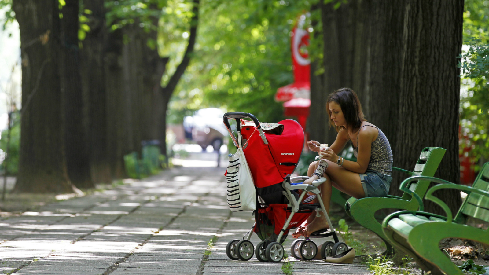 A woman feeds her child in a park in Bucharest June 7, 2013. REUTERS/Bogdan Cristel (ROMANIA - Tags: SOCIETY)