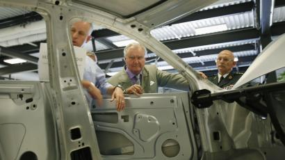 Prince Consort Henrik of Denmark (C) inspects the chassis of the Tesla Model S electric vehicle.
