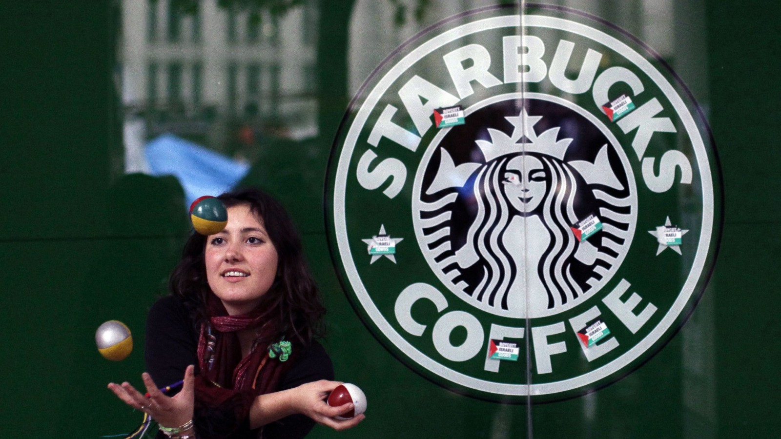 A French supporter of the Occupy London Stock Exchange movement who gave her name as Estelle de Marseille, stating that it's the name she goes by but not her real name, juggles outside a branch of the Starbucks coffee chain beside the protest camp outside St Paul's Cathedral London, Thursday, Oct. 27, 2011