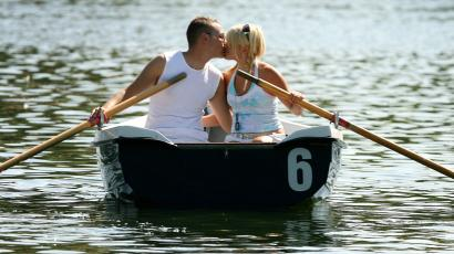 A couple enjoy a day out on the Serpentine boating lake in London