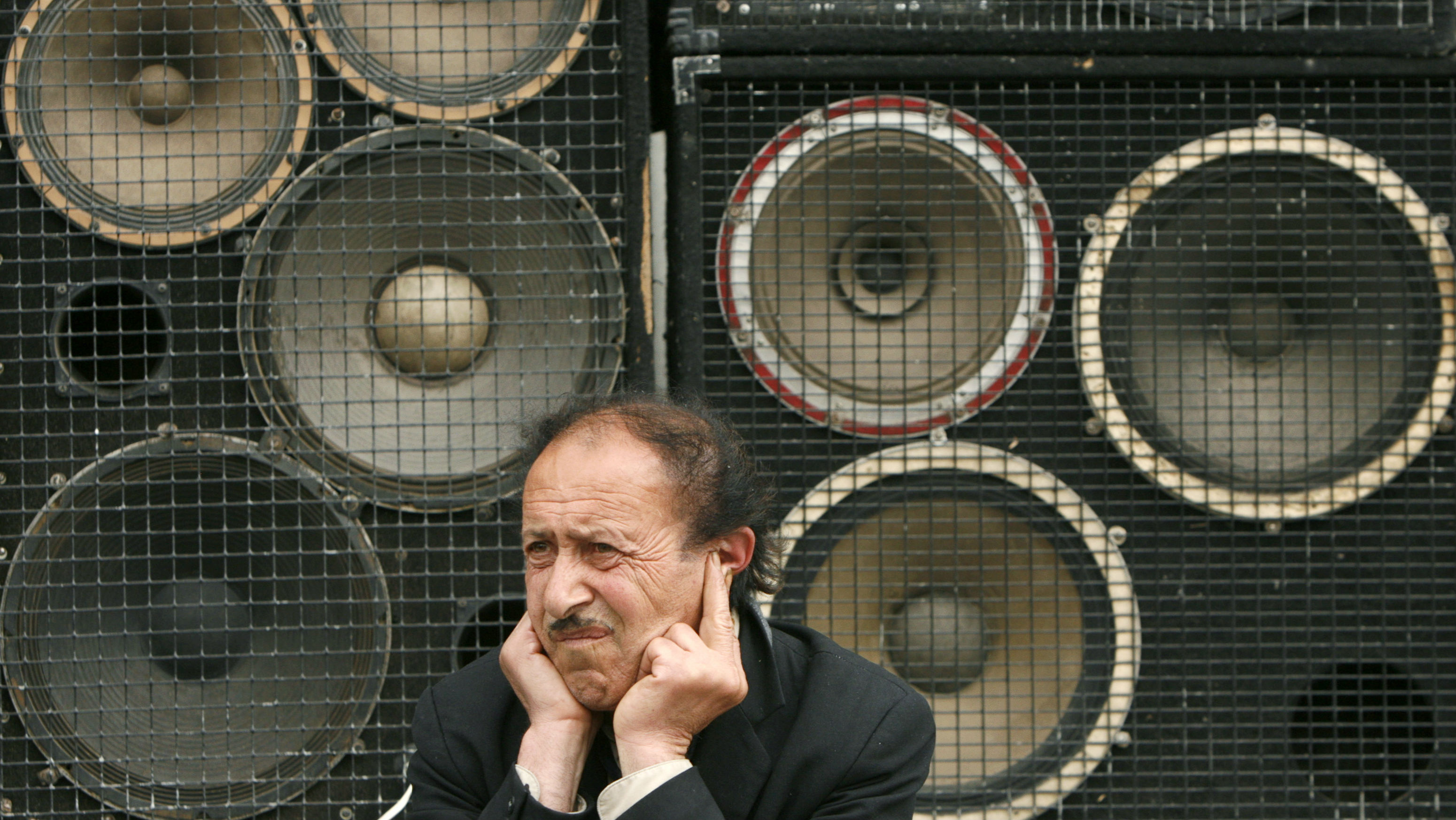 A man protects his ears as he sits in front of loud speakers during an opposition rally in central Yerevan May 13, 2007. Pro-presidential parties have won a large majority in Armenia's parliamentary elections, the country's election commission said on Sunday, a vote Western monitors described as a vast democratic improvement. REUTERS/David Mdzinarishvili (ARMENIA)