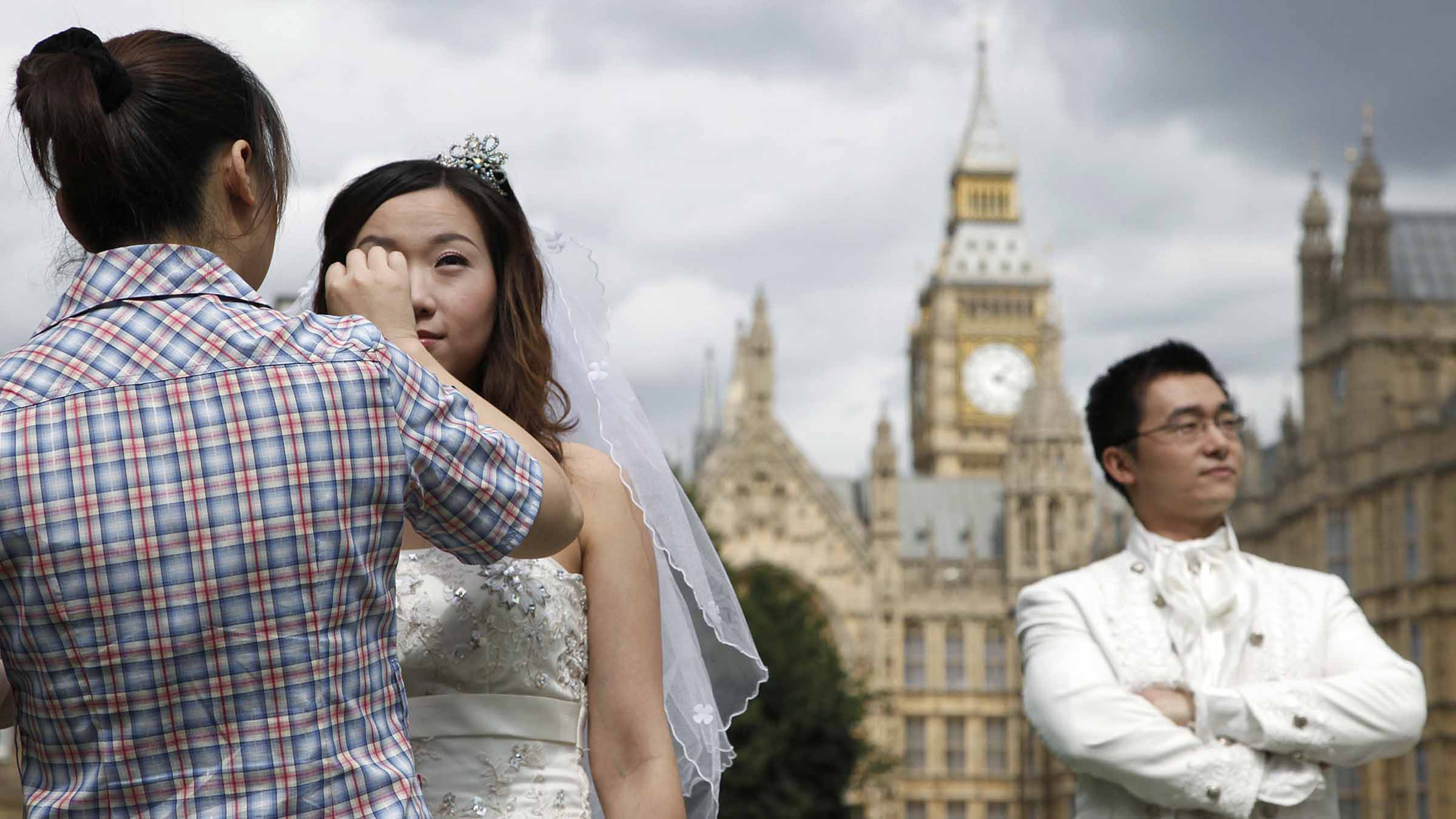 A bride has her make up retouched as her husband waits before a wedding photo shoot outside the Houses of Parliament in London