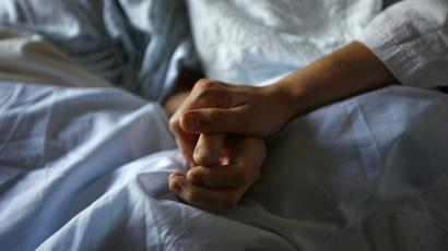 HEADLINE:A woman holds the hand of her mother who is dying from cancer during her final hours at a palliative...