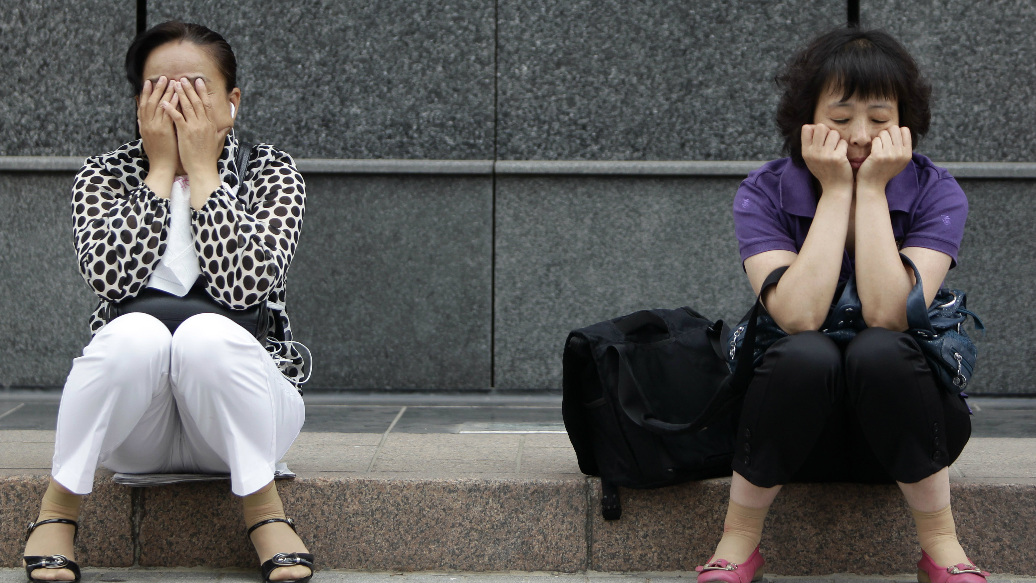 Mothers take a nap near a school as their children take the National College Entrance Exams in Beijing.