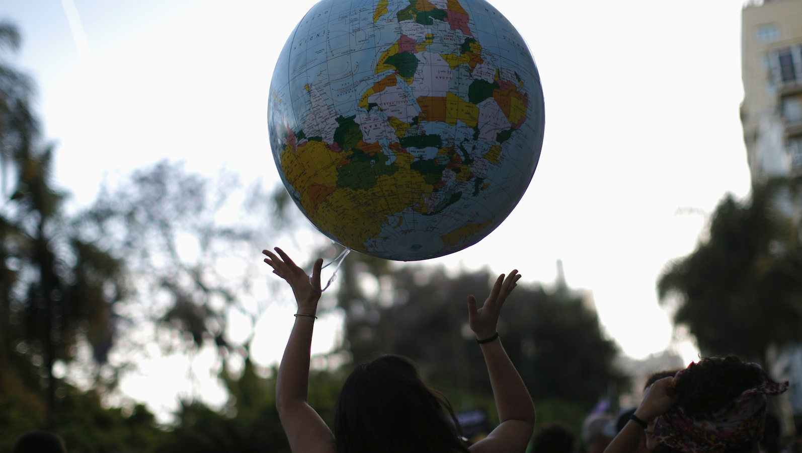 """Ana Navarro, 33, plays with a giant inflatable balloon of planet Earth as she takes to the streets during a protest march marking the first year anniversary of Spain's Indignados (Indignant) movement in Malaga, southern Spain May 12, 2012. Dubbed """"los indignados"""" (the indignant), the movement which spawned similar protests worldwide prepare to occupy Spanish streets for the whole weekend on the first anniversary of the 15M movement in a renewed protest over  government austerity measures, banks, politicians, economic recession, and the highest unemployment in the eurozone. REUTERS/Jon Nazca (SPAIN - Tags: ANNIVERSARY CIVIL UNREST POLITICS SOCIETY BUSINESS EMPLOYMENT) - RTR31Z15"""