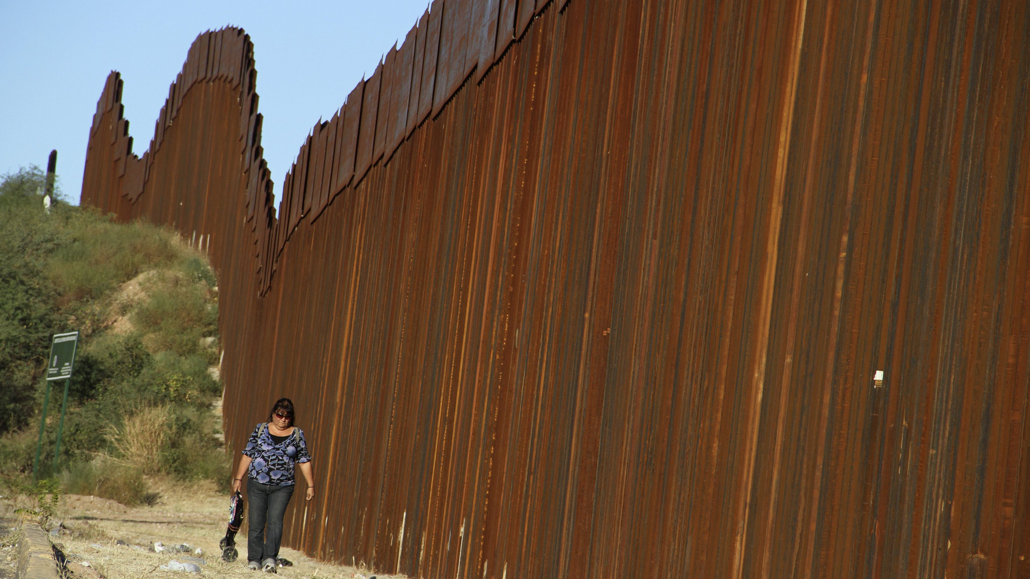 A woman walks past the border fence between Mexico and the U.S. in Nogales
