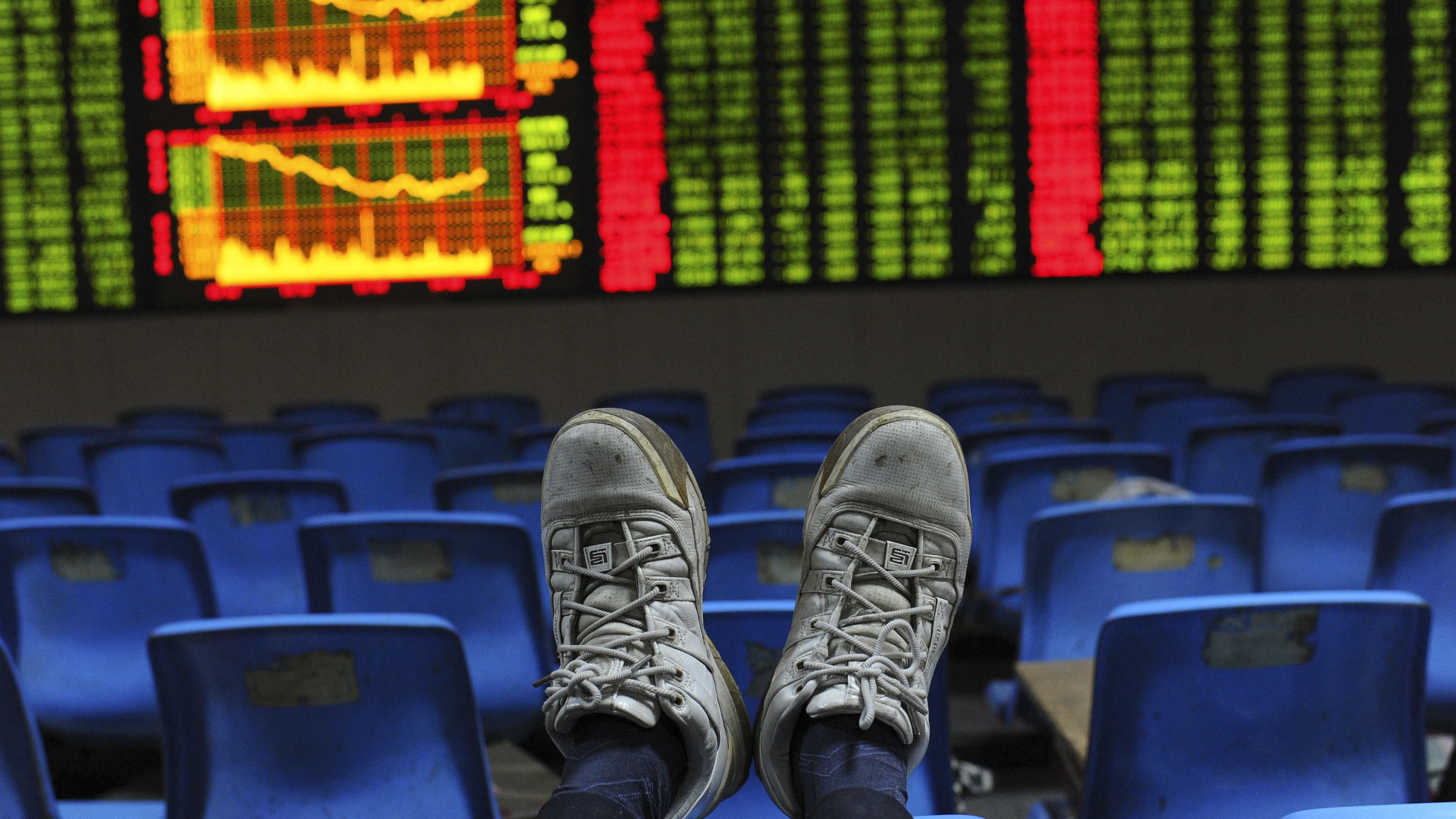 An investor puts his feet onto the back of a chair in front of an electronic board displaying stock information at a brokerage house in Hefei, Anhui province October 26, 2012.