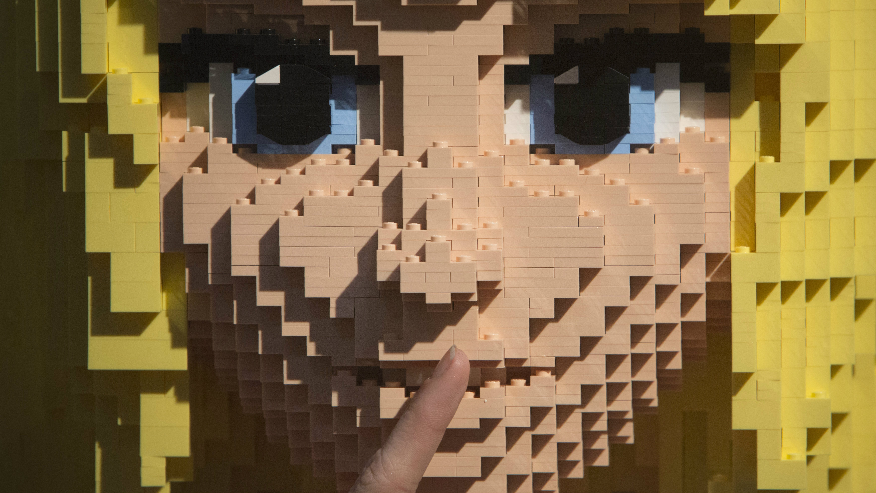 """A consumer touches the face of Lego Friends sculpture """"Stephanie"""" at Toy Fair 2013 in New York."""