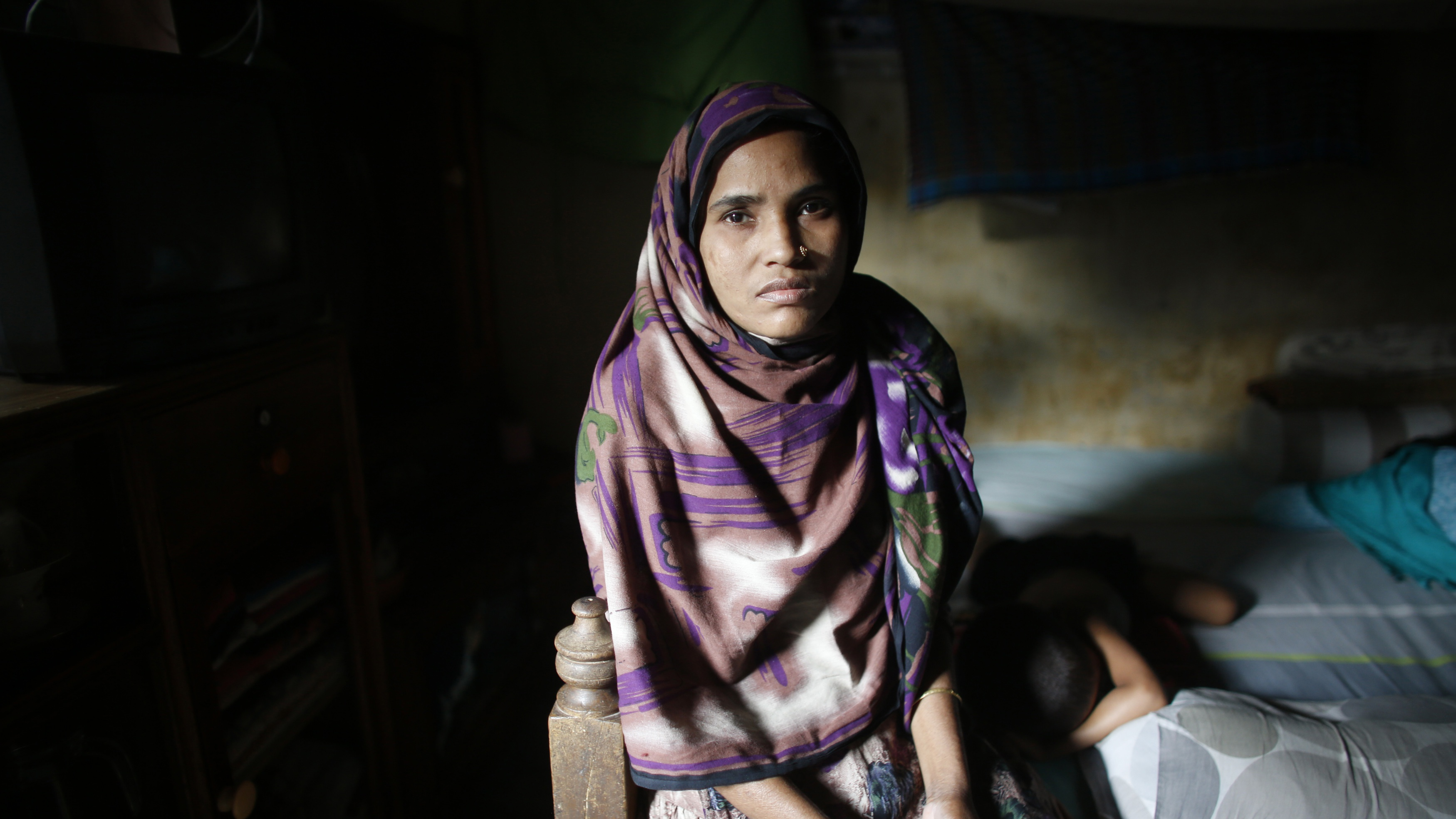 Nilufar Yesmin, 36, who was rescued from the rubble of the collapsed Rana Plaza building, sits inside her slum house in Savar April 21, 2014. Nilufar, who is unable to work due to a spinal injury sustained from the accident last year, says she has not received any compensation. Survivors of the world's worst garment factory accident, struggle to rebuild their lives from the rubble of the Rana Plaza collapse as Bangladesh readies to mark the first anniversary of the disaster that killed more than 1,100 people. Survivors of the tragedy are still haunted by the memories of the fateful day. The efforts to compensate victims and inspect factories remain frustratingly slow and erratic.