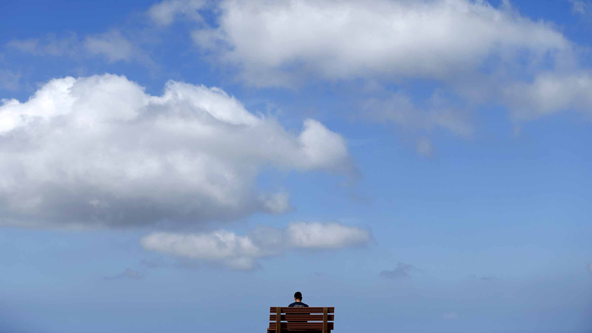 A young man sits high atop a hill reading a book on a park beach as the clouds pass overhead in San Marco, California