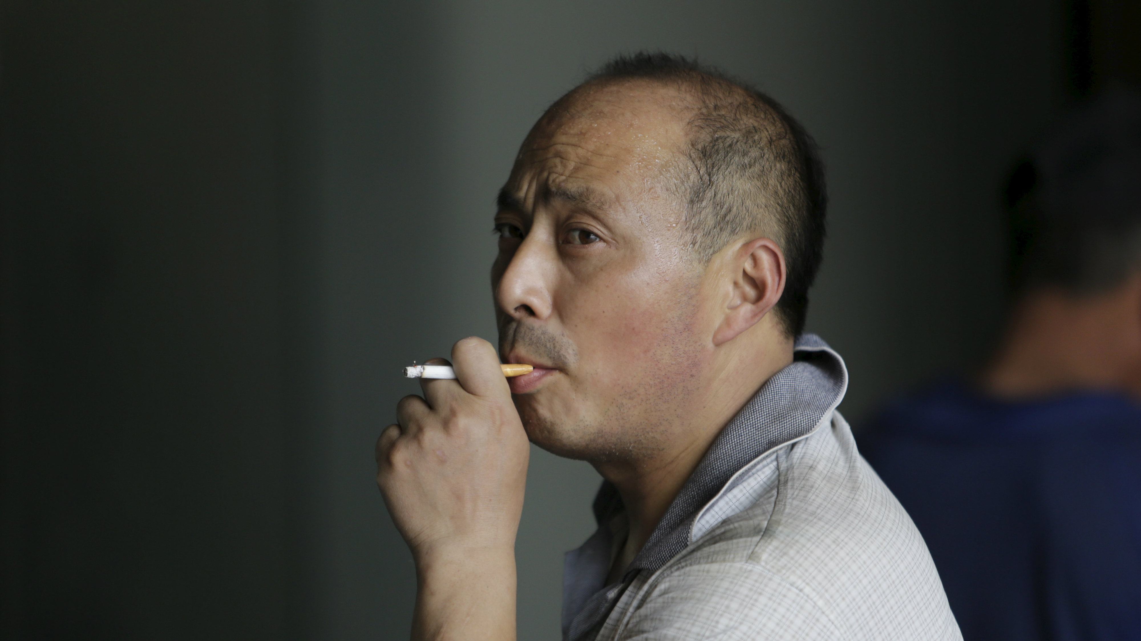 A man smokes a cigarette outside an office building in Beijing.