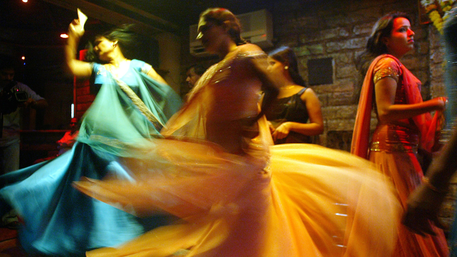 """Indian bar girls perform at a dance bar in Bombay May 5, 2005. The government of the western Indian state of Maharashtra on Wednesday endorsed the decree seeking to ban dance bars in the state. There are more than 600 dance bars in Bombay itself and the closure of cabarets is likely to render jobless more than 150,000 people across the state including dancers, waiters, bouncers and security guards. Most Bars in the state employ girls, who dress in colourful costumes and dance to Bollywood songs, as customers shower them with currency bills. According to bar girl's union, majority of the 75,000 girls working in bars will be forced into the """"flesh trade"""" due to the closure. Picture taken on May 5, 2005."""
