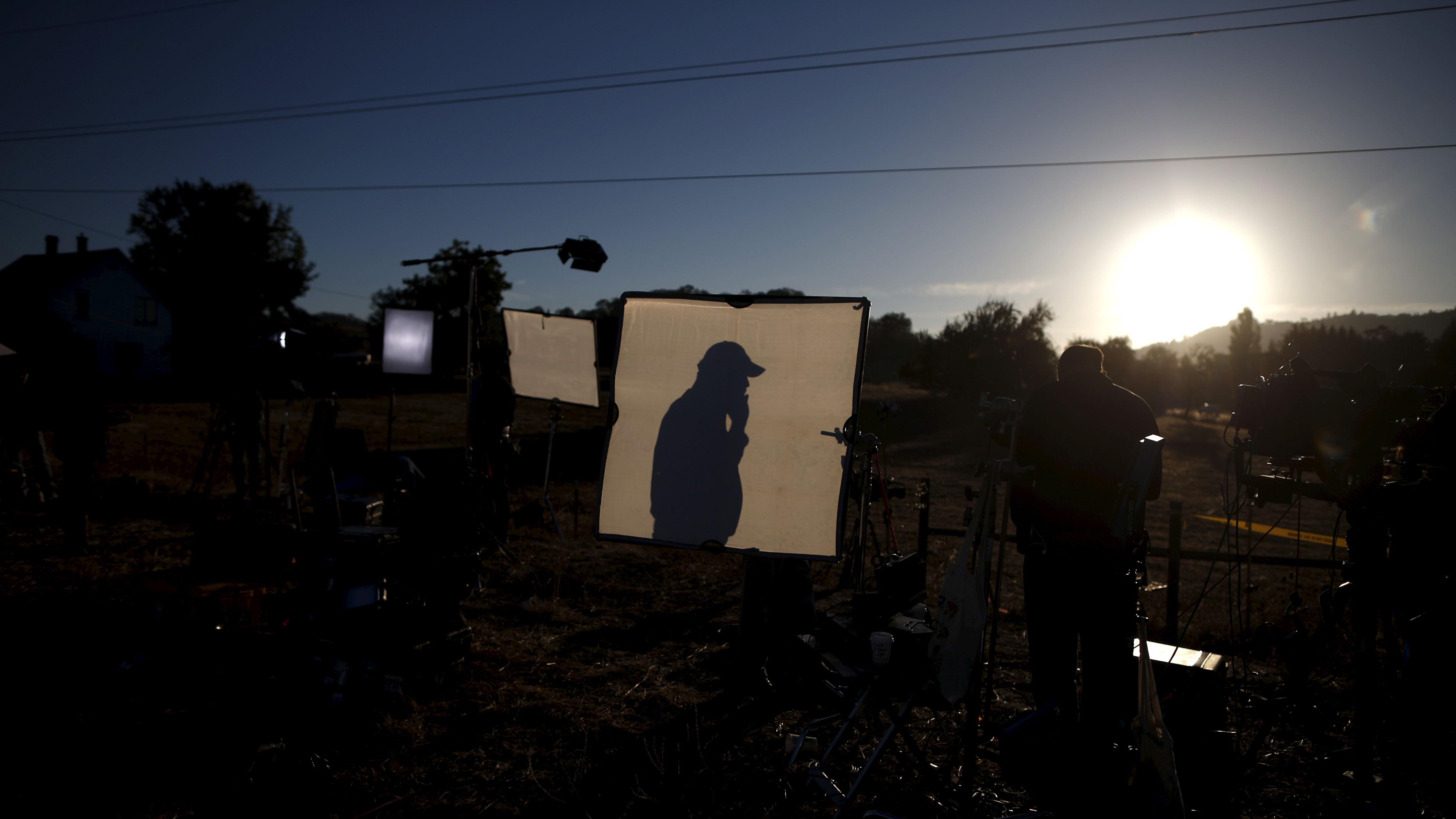 Television crews film at sunrise outside Umpqua Community College in Roseburg