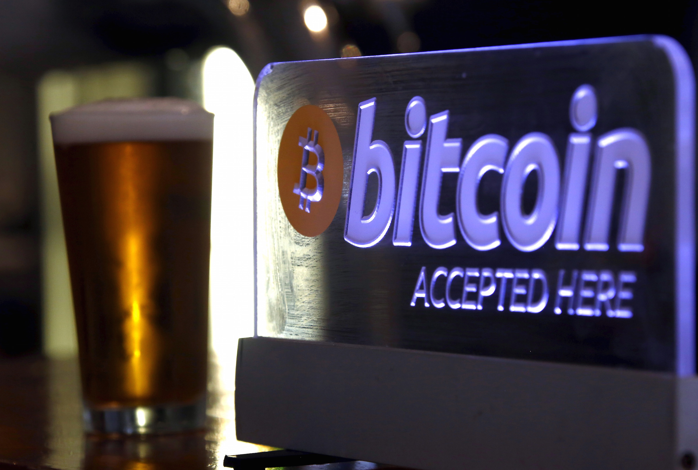 A beer poured for a customer sits on a bar next to a Bitcoin sign in central Sydney, Australia, September 29, 2015. Australian businesses are turning their backs on bitcoin, as signs grow that the cryptocurrency's mainstream appeal is fading. Concerns about bitcoin's potential crime links mean many businesses have stopped accepting it, a trend accelerated by Australian banks' move last month to close the accounts of 13 of the country's 17 bitcoin exchanges. Picture taken September 29, 2015. REUTERS/David Gray