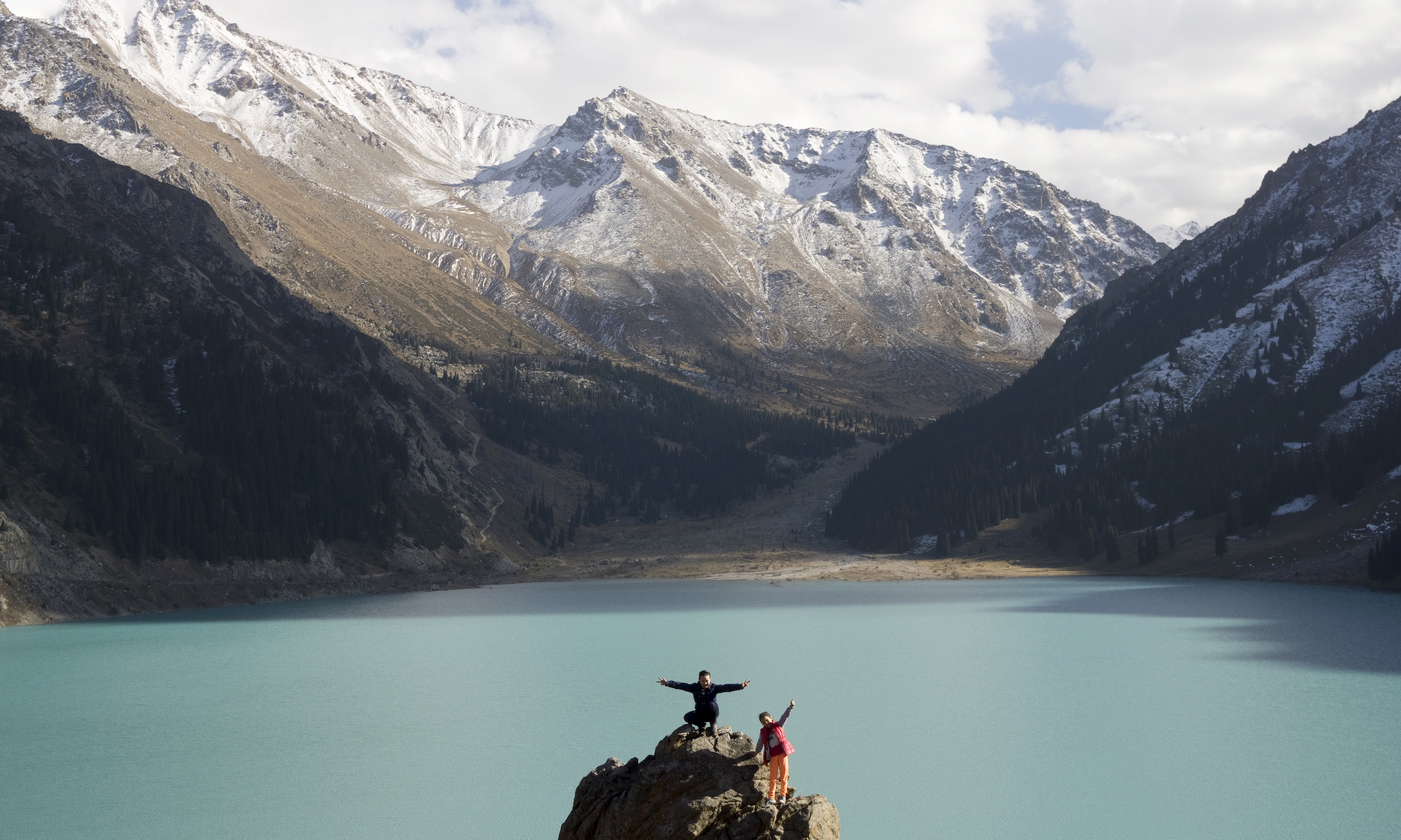 Children pose for their parents on a rock in front of the Bolshoy (Big) Almaty lake at 2,600 (8530 ft) meters above sea level at a sunny autumn day in a mountains outside Almaty, Kazakhstan, October 4, 2015.  REUTERS/Shamil Zhumatov      TPX IMAGES OF THE DAY      - RTS2Y8K