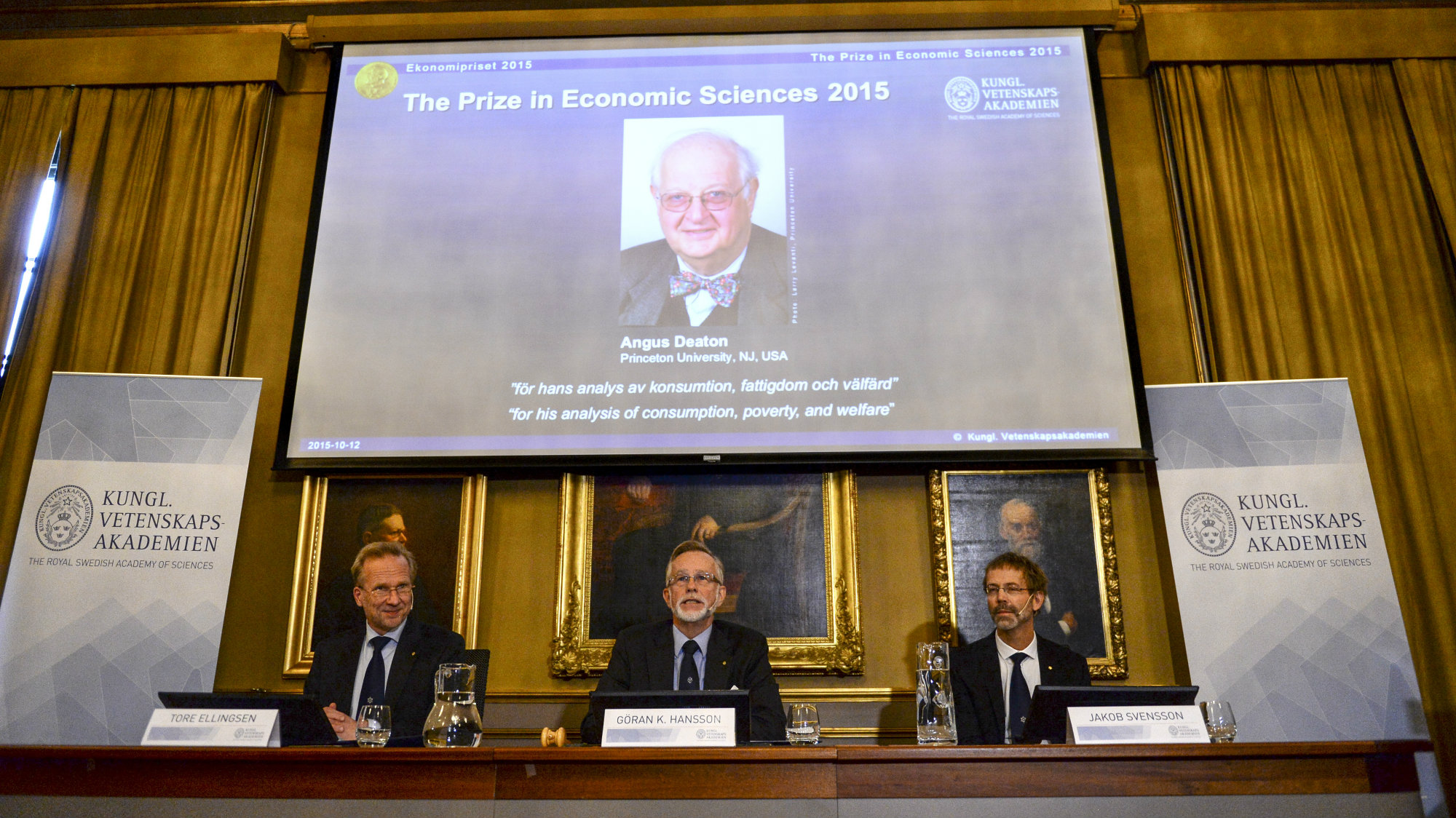 """A picture of British economist Angus Deaton, winner of the 2015 economics Nobel Prize, is seen on a screen as Goran K. Hansson (C), permanent secretary for the Royal Swedish Academy of Sciences, and Tore Ellingsen (L), chairman of the prize committee, and Jakob Svensson, member of the Academy, address a news conference at the Royal Swedish Academy of Science, in Stockholm, Sweden October 12, 2015. Deaton won the 2015 economics Nobel Prize for """"his analysis of consumption, poverty, and we"""
