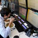 A trader eats lunch at his desk at a brokerage in Sao Paulo, Brazil.