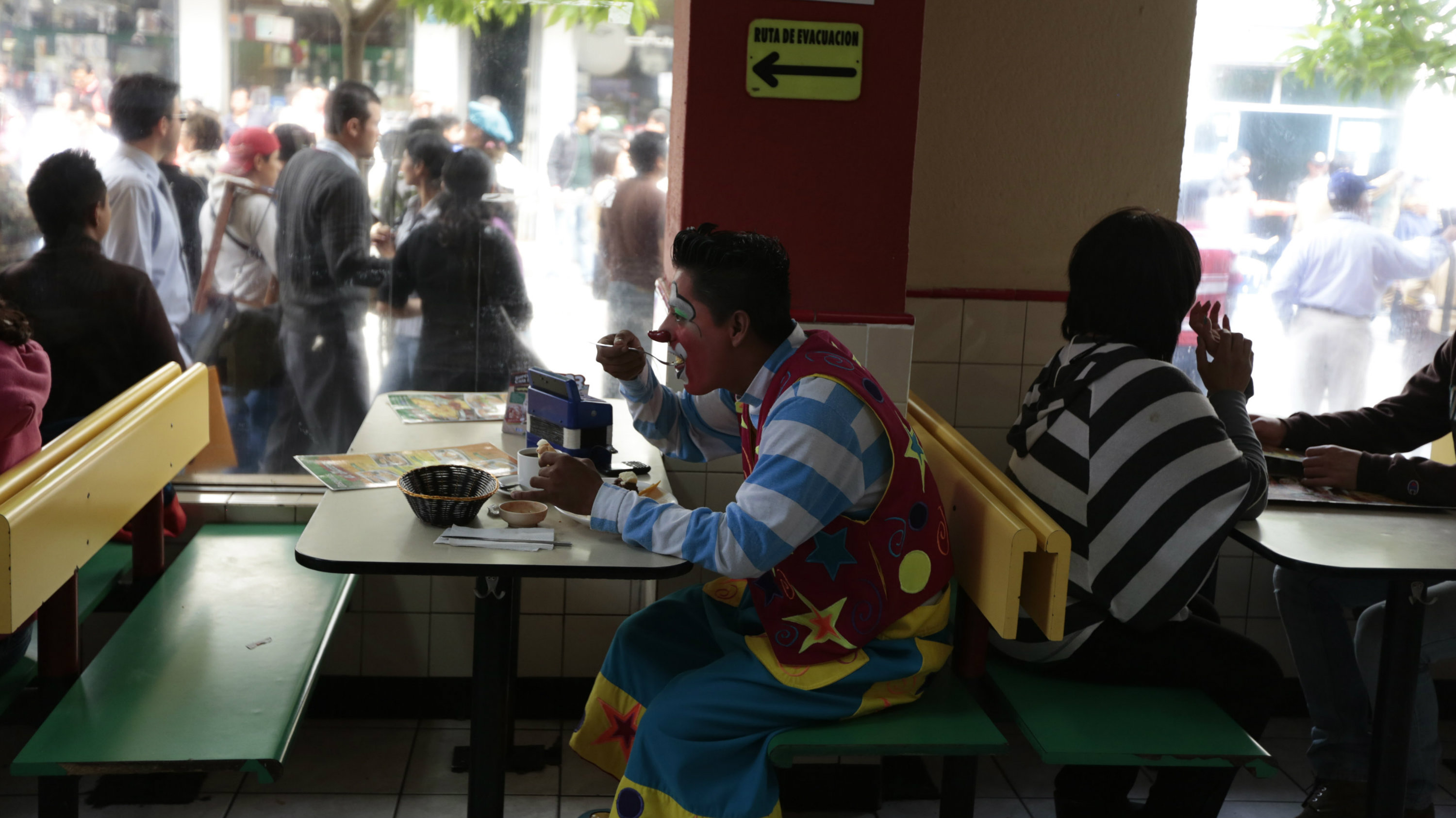 A clown has his breakfast before participating in a parade to inaugurate the 5th Annual Clowns' Convention in Guatemala City, July 23, 2013.