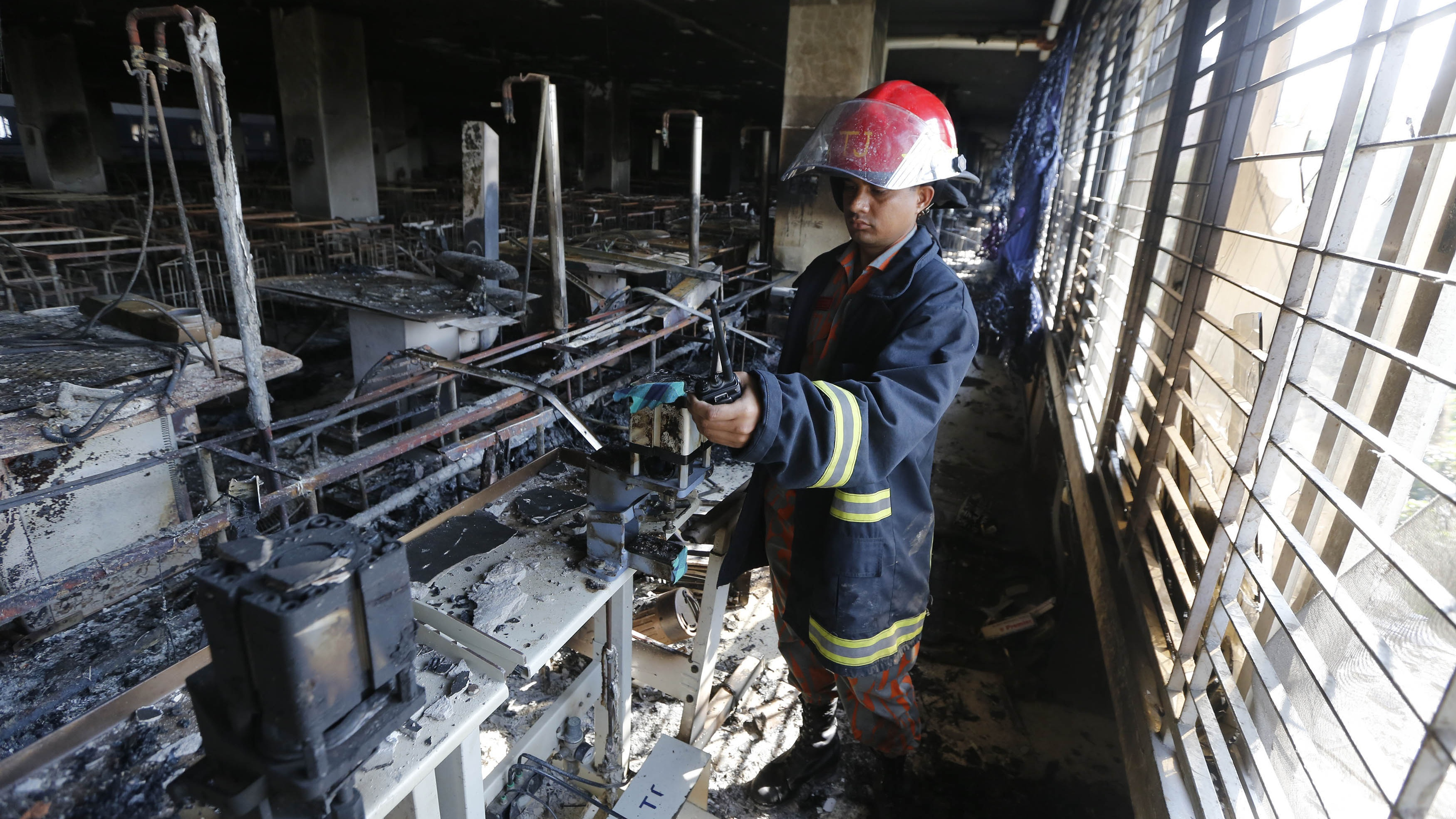 A firefighter inspects the Standard Group garment factory which was on fire in Gazipur November 29, 2013. A huge fire on Friday destroyed the Bangladesh garment factory supplying key Western brands, authorities said, in a blaze touched off by workers angered over rumours of a colleague's death in police firing. There were no initial reports of casualties in the fire.
