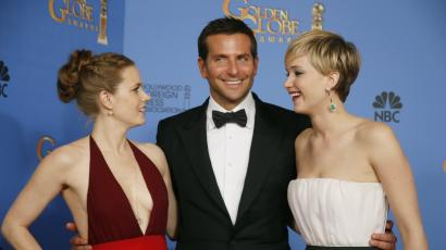 """American Hustle"" stars Amy Adams (L), Bradley Cooper and Jennifer Lawrence pose after the Golden Globe awards."