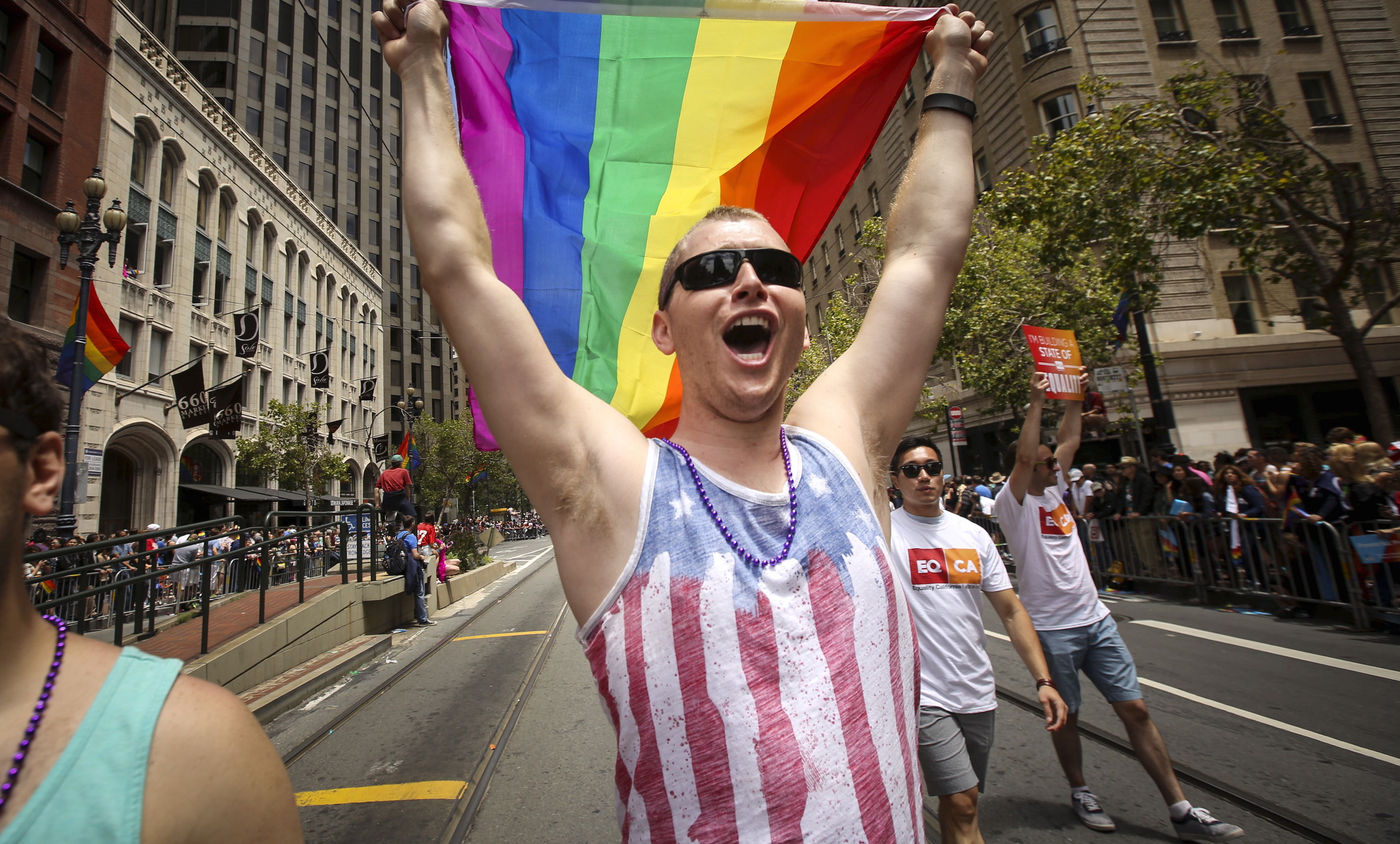 A man waves a rainbow flag while marching in the San Francisco gay pride parade two days after the U.S.  Supreme Court's landmark decision that legalized same-sex marriage throughout the country in San Francisco, California June 28, 2015.  REUTERS/Elijah Nouvelage - RTX1I6KA
