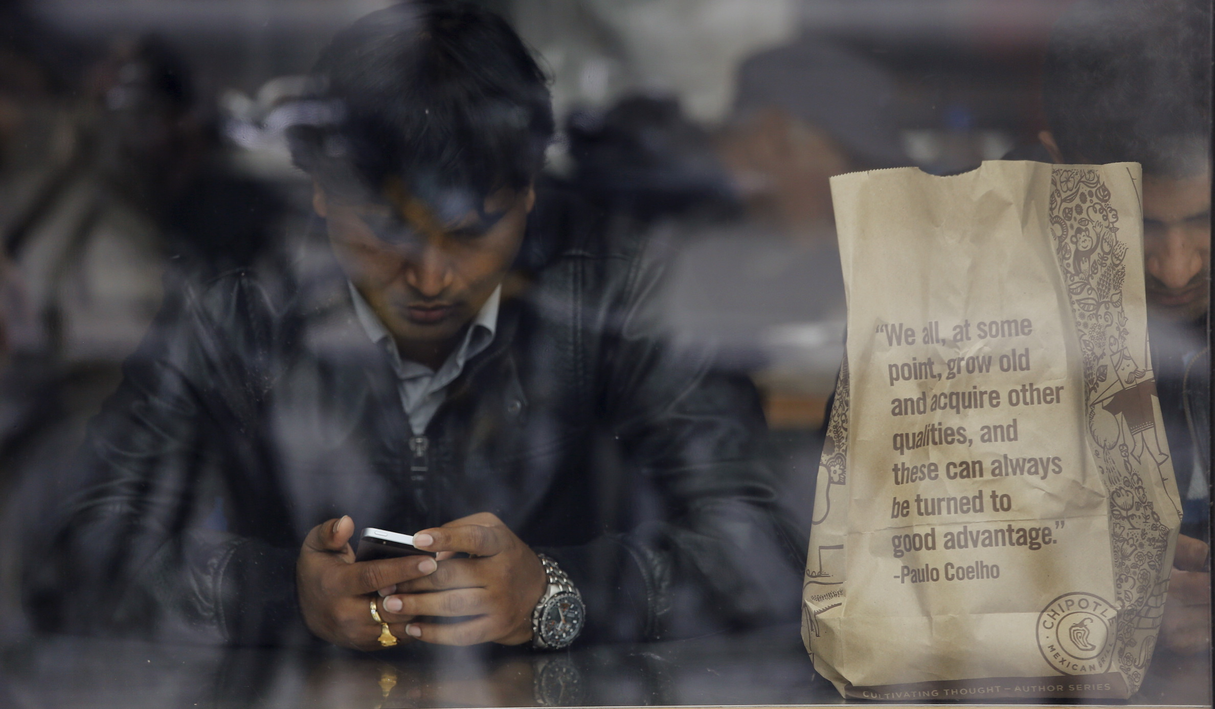 A man uses his phone next to a bag of food from Chipotle Mexican Grill in San Francisco, California July 21, 2015. Burrito chain Chipotle Mexican Grill Inc reported lower-than-expected quarterly revenue on Tuesday.   REUTERS/Robert Galbraith - RTX1L9VC