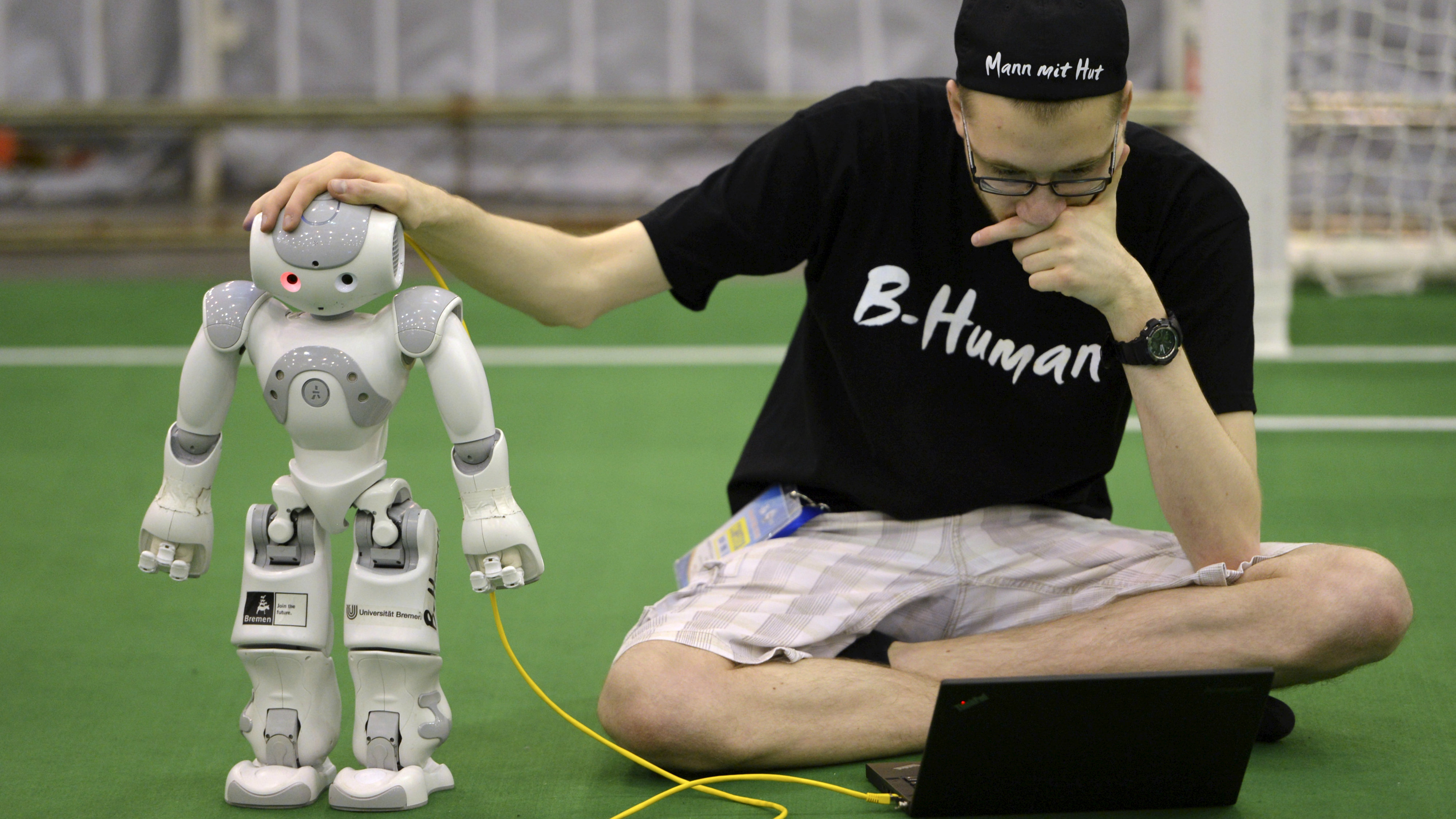 "A member from a German team adjusts a humanoid robot during the 2015 Robocup finals in Hefei, Anhui province, July 22, 2015. The Robocup, or ""Robot Soccer World Cup"", is an annual international robotics competitions which is held between July 17 - 23 this year in China's Hefei"