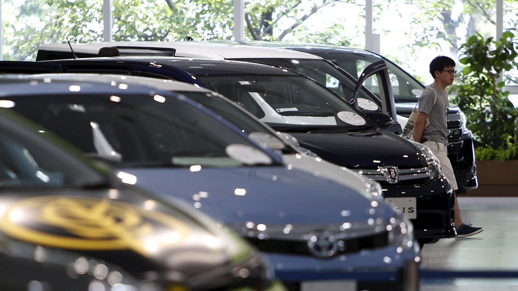 A visitor walks past Toyota Motor Corp's cars displayed at the company's showroom.