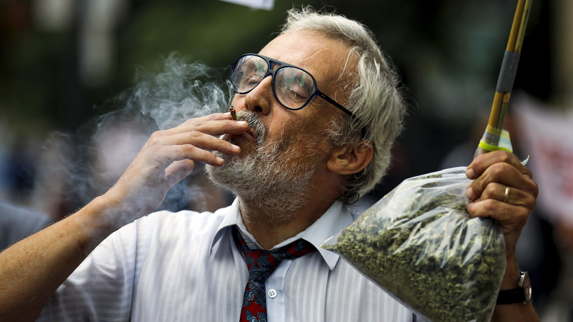 Activist Ray Turmel holds a bag of medical marijuana while he smokes a marijuana cigarette, as he calls for the total legalization of marijuana, outside the building where the federal election Munk Debate on Canadaís Foreign Policy is being held in Toronto, Canada September 28, 2015.