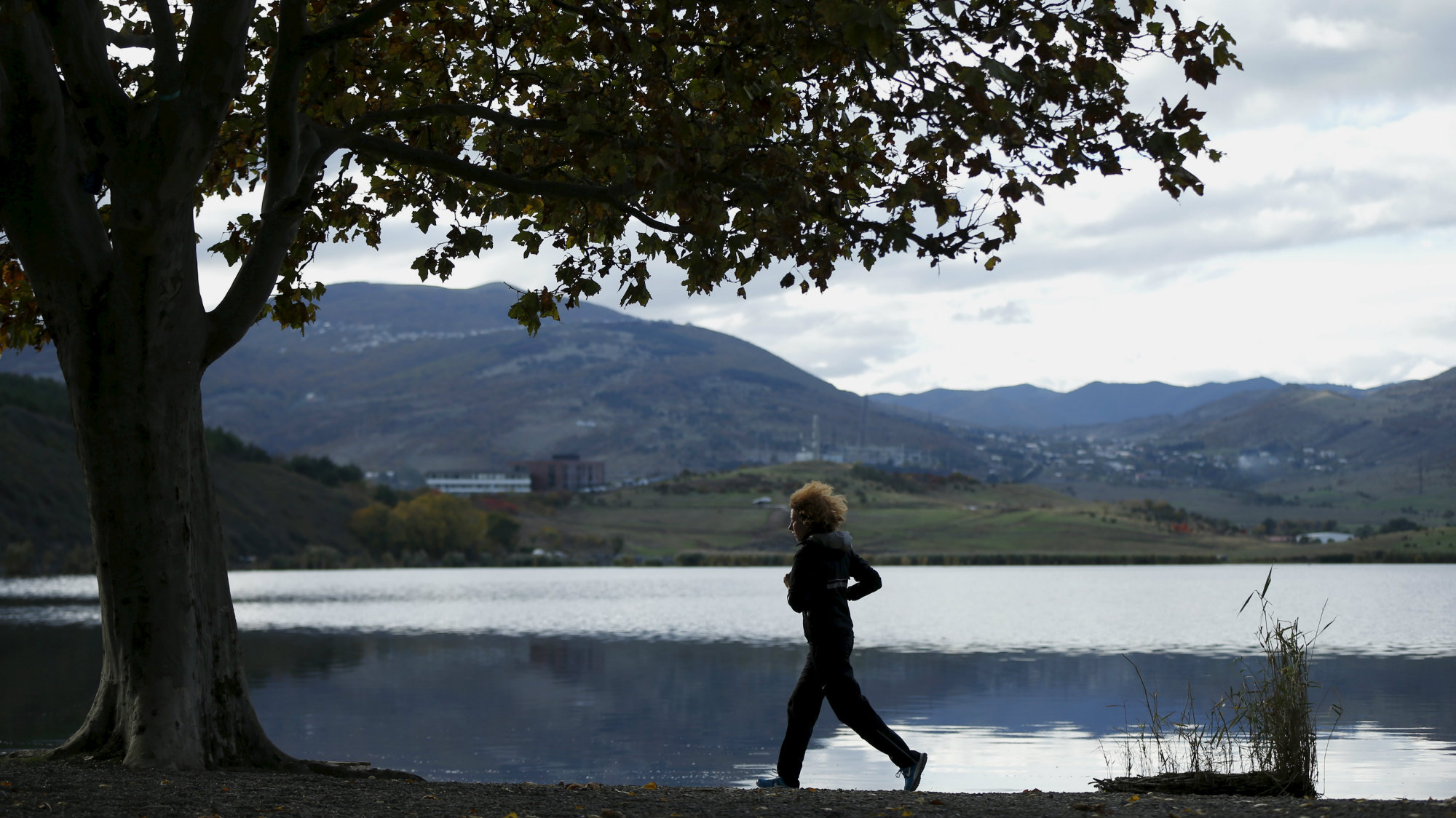 A woman jogs on the banks of the Lisi Lake in Tbilisi