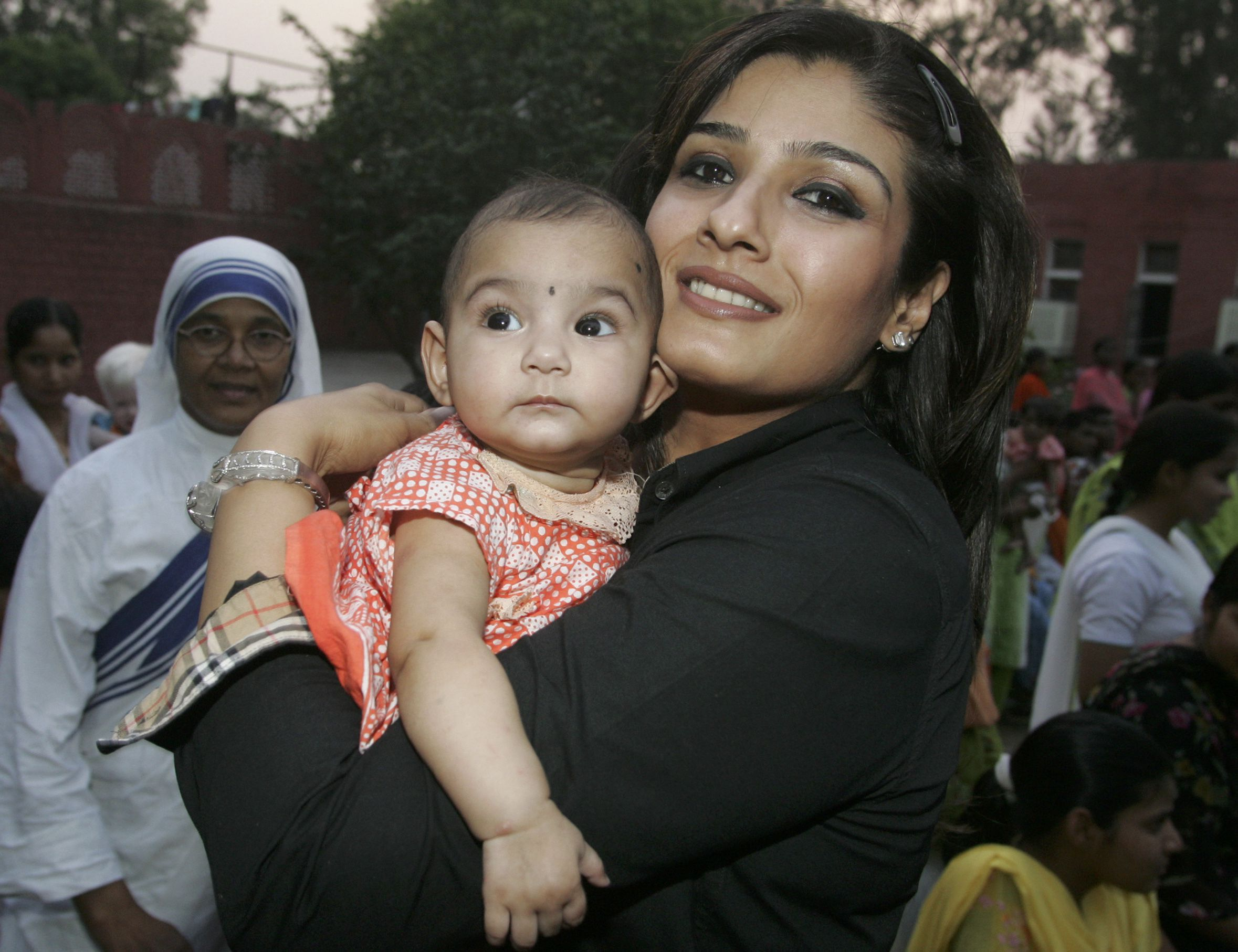 Bollywood actress Raveena Tandon holds a child during her visit at Mother Teresa orphanage in the northern Indian city of Chandigarh May 15, 2008. REUTERS/Ajay Verma (INDIA) - RTX5QWW