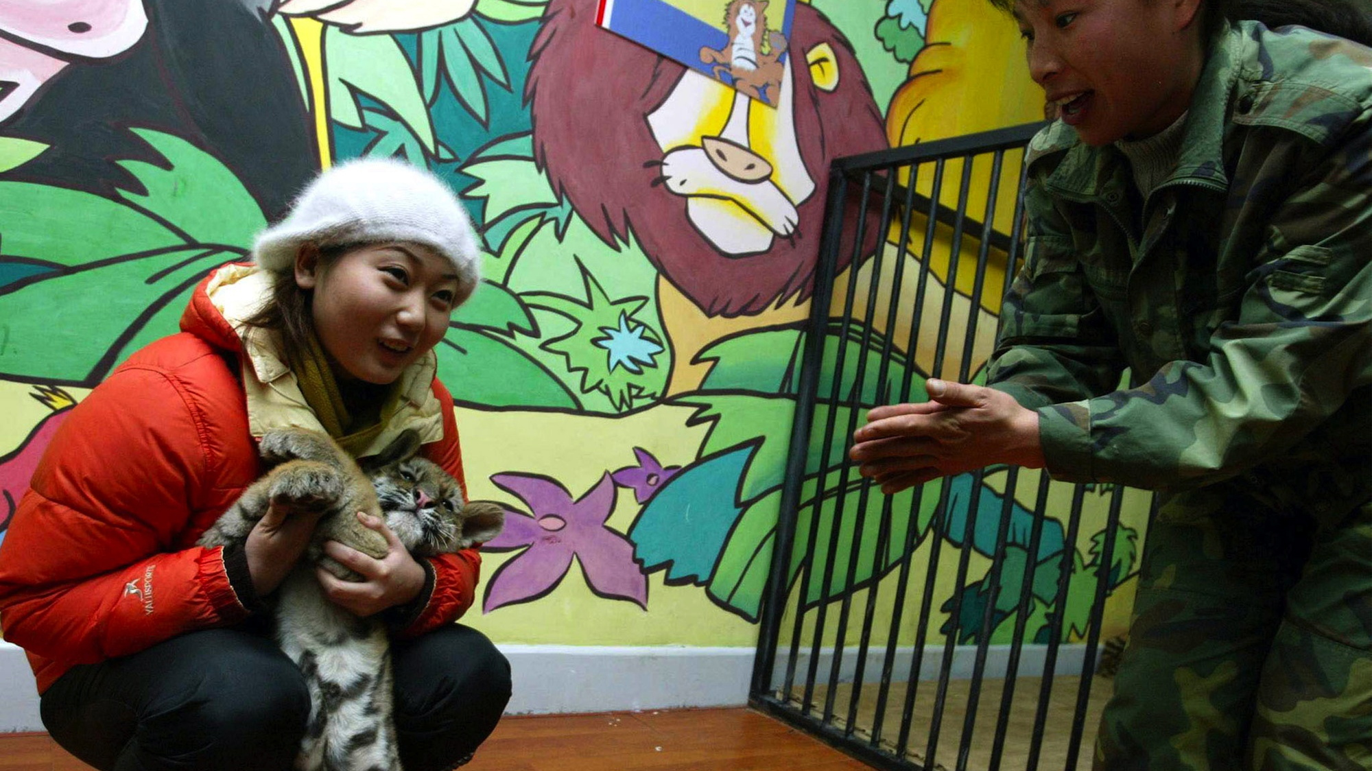 A customer plays with a tiger cub at a shopping centre in Shenyang December 12, 2002.
