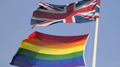 A rainbow flag flies with the Union flag above British Cabinet Offices.