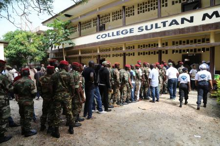 Guinean soldiers and civilians queue to cast their votes in Conakry.
