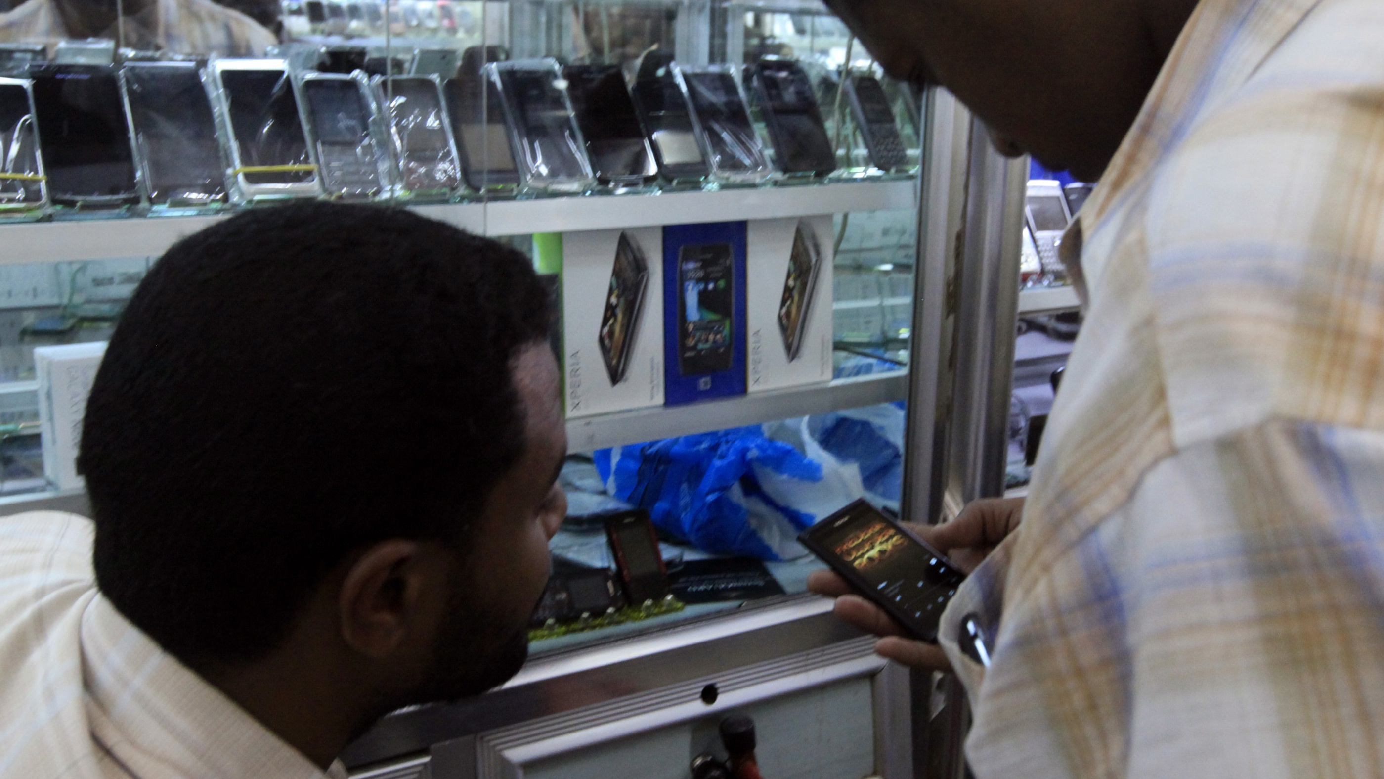 A vendor shows a cell phone to a customer in his store in Khartoum, Sudan.